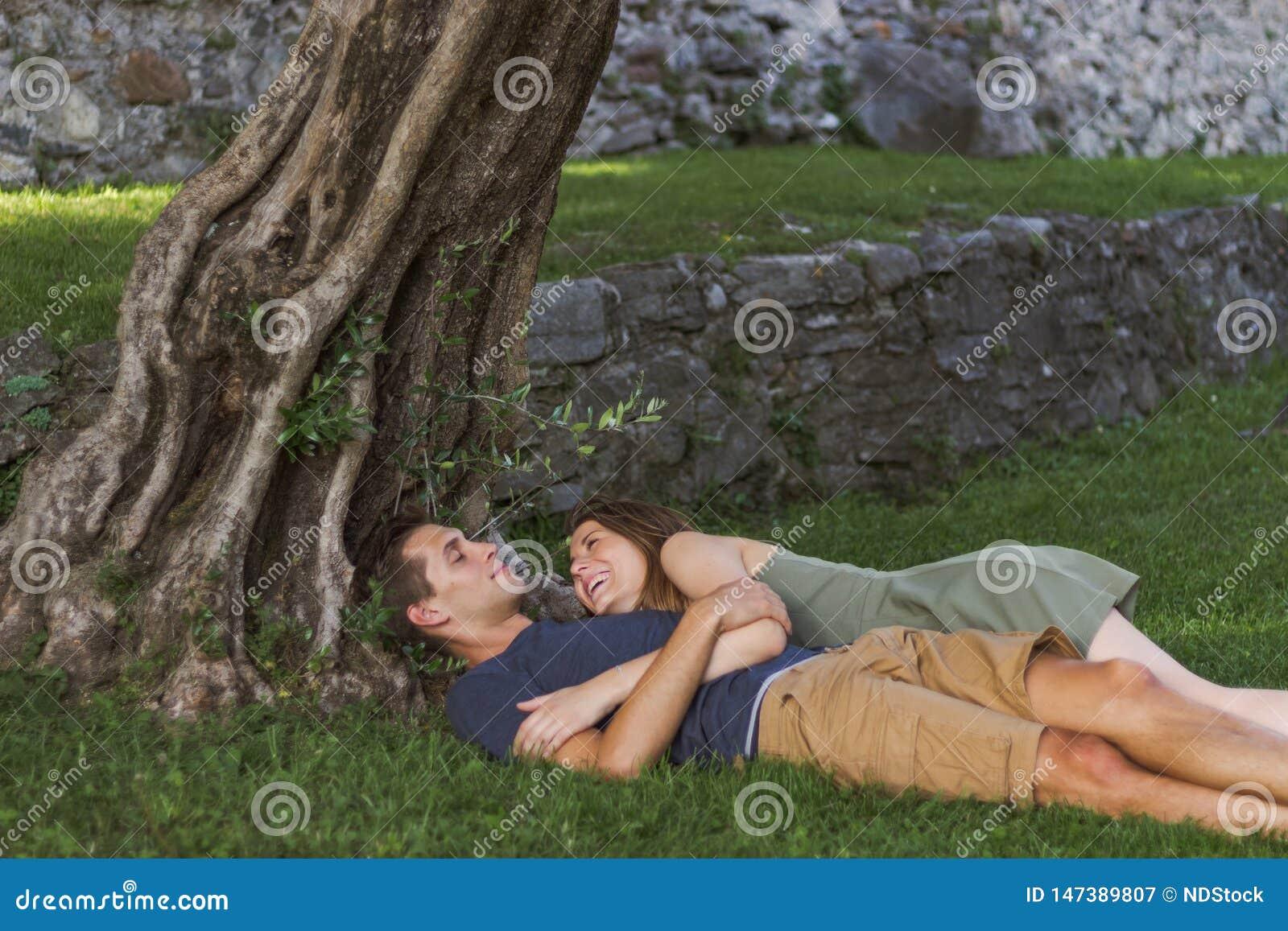 年轻人在坐在城堡的一棵树下的爱结合