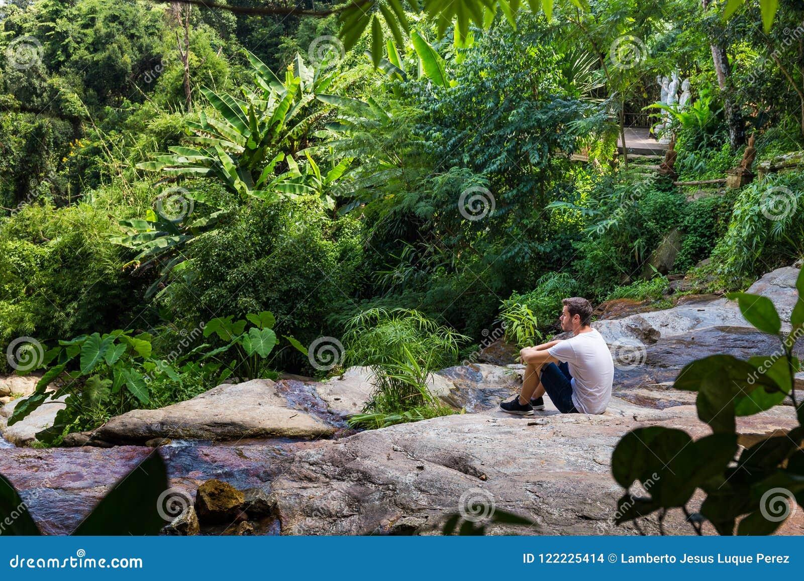 年轻人坐瀑布在清迈密林