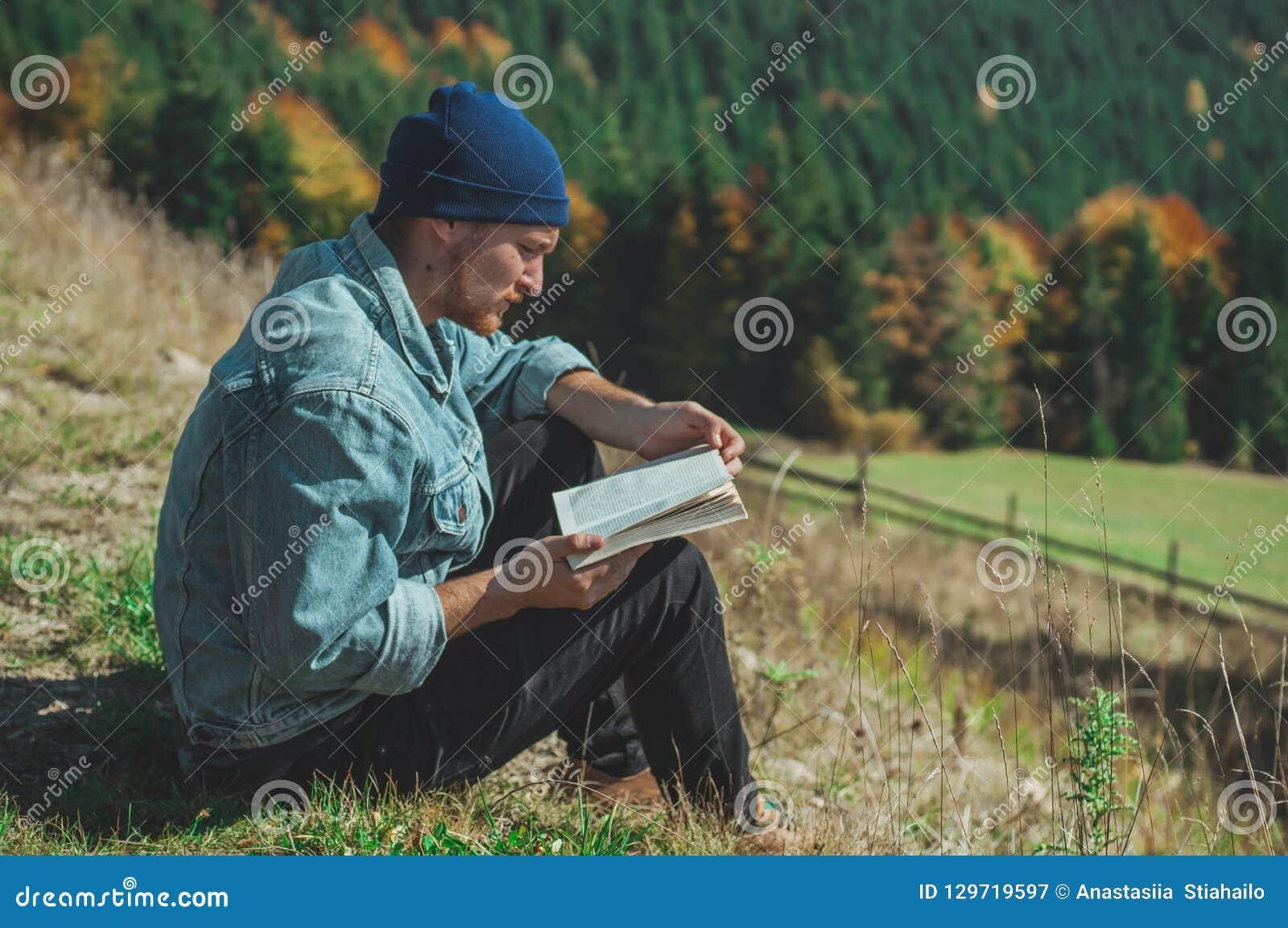 年轻人旅客看书,在背景暑假和生活方式概念的室外山