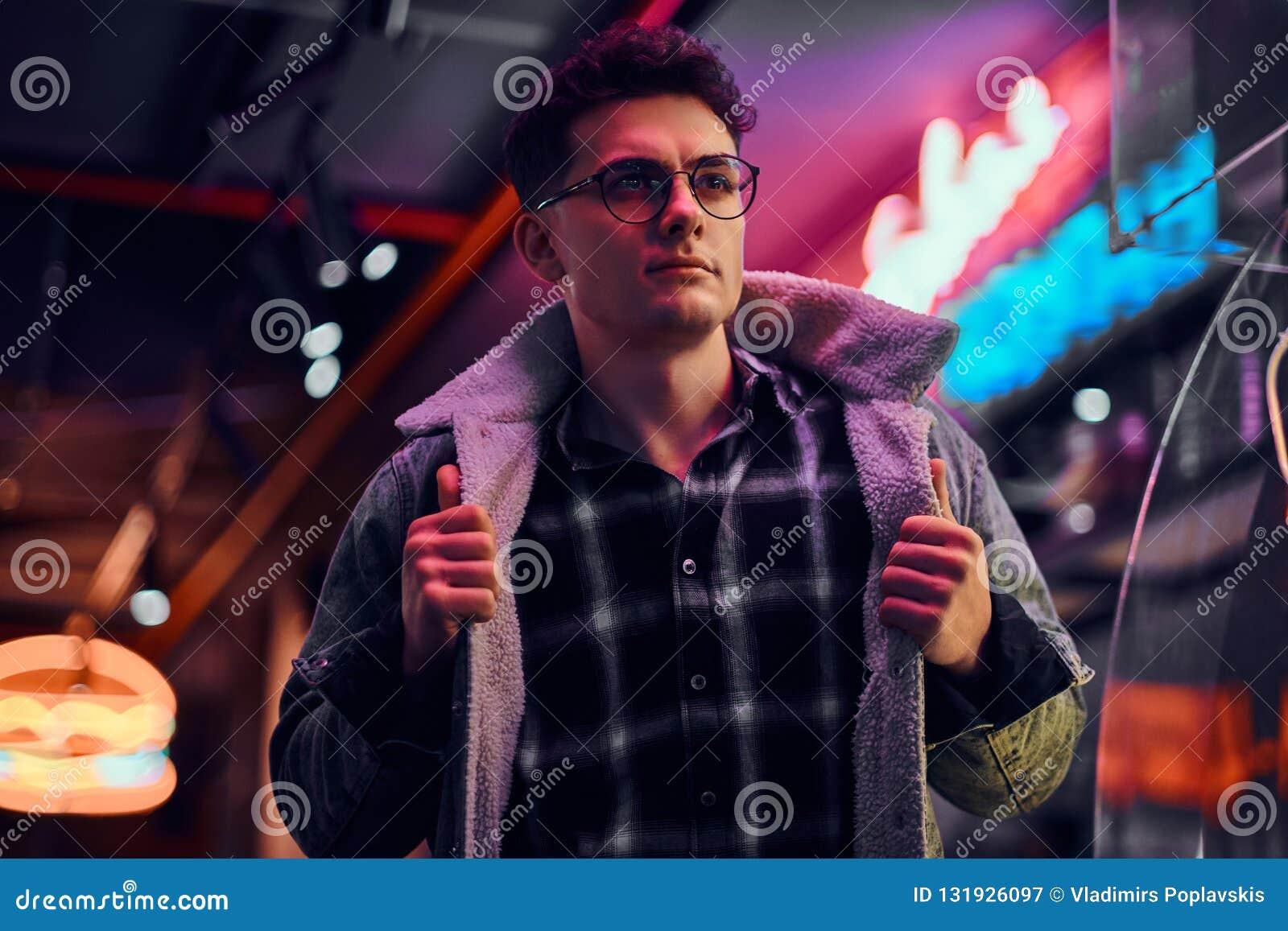 年轻人时兴地在晚上穿戴了在街道的身分 有启发性牌,氖,光