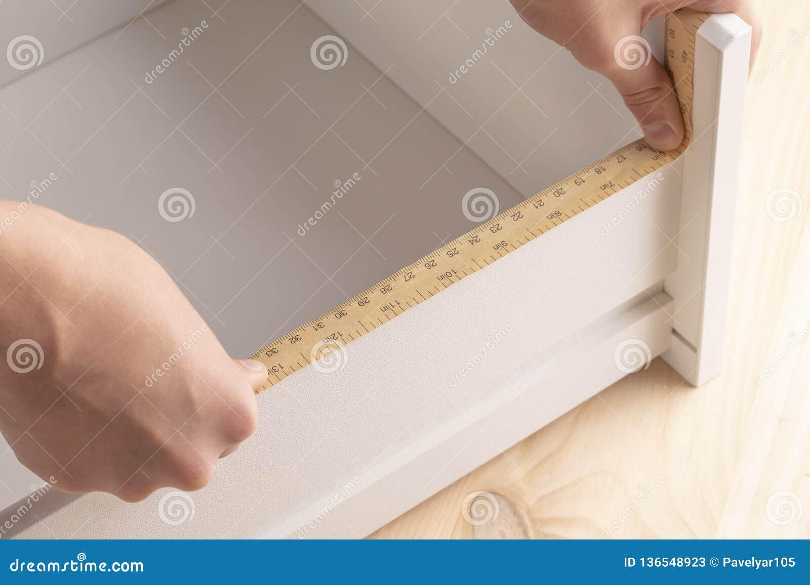 年轻人测量与一个测量的工具的架子