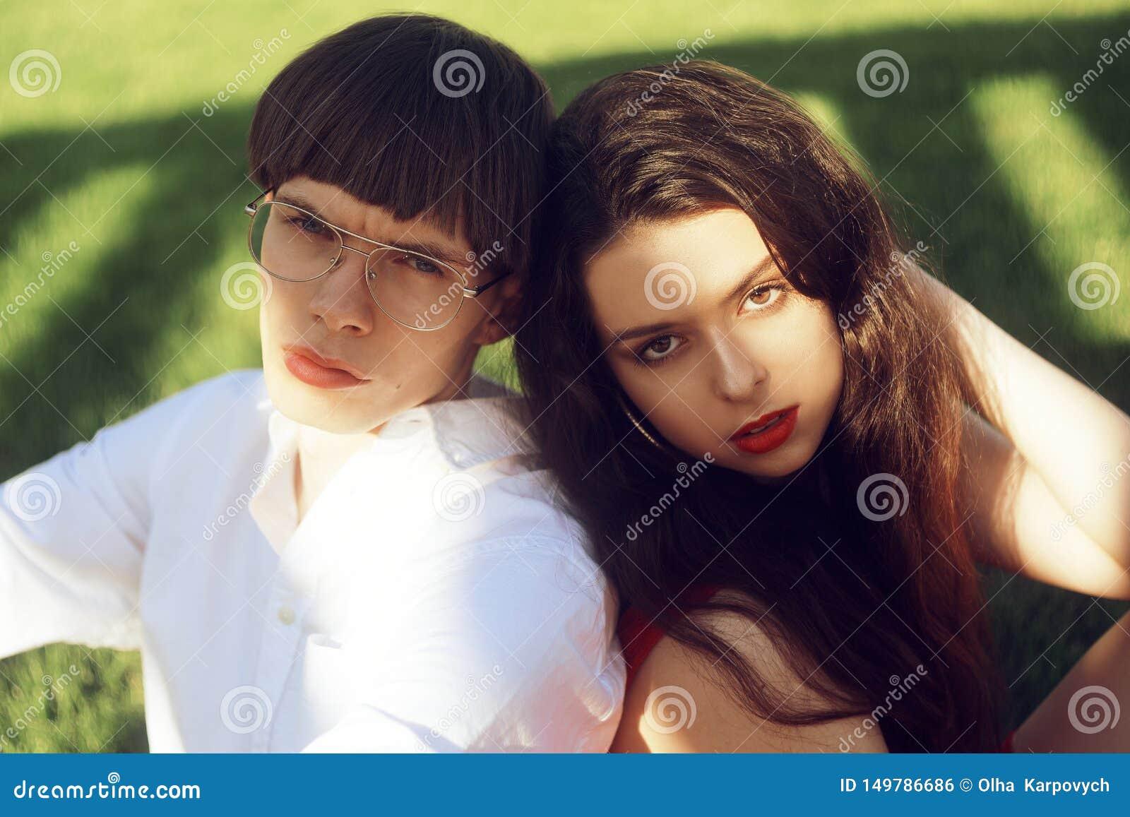 年轻人浪漫夫妇草的在公园 放松在绿草的愉快的夫妇 ?? 有红色嘴唇的一个女孩 ??