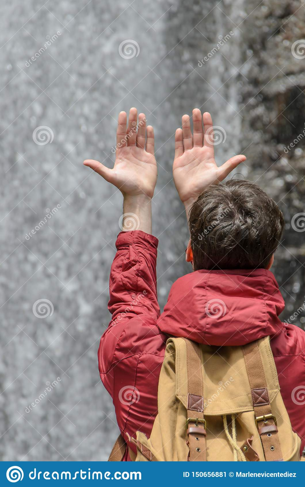 年轻人用手被举往水瀑布