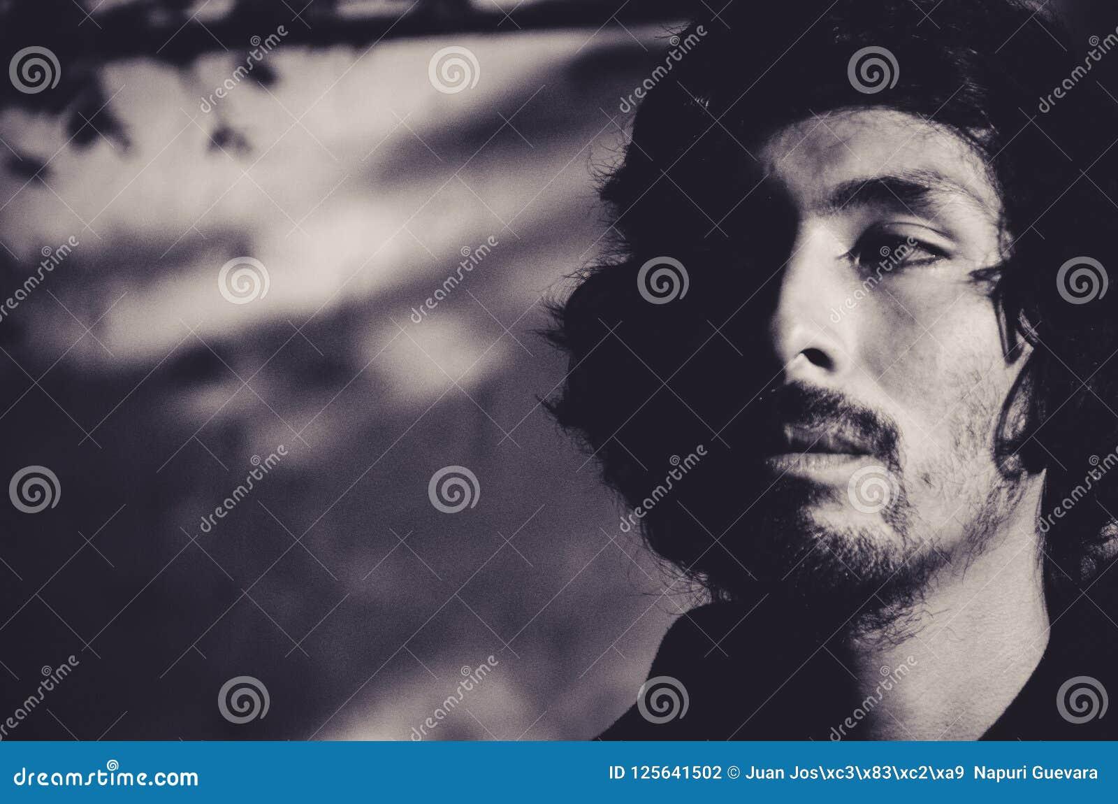 年轻人画象有胡子佩带的衬衣的和有树的阴影的