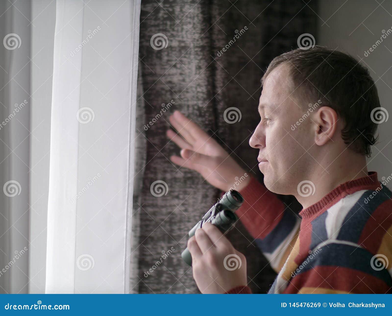 年轻人看与双筒望远镜的窗口,特写镜头