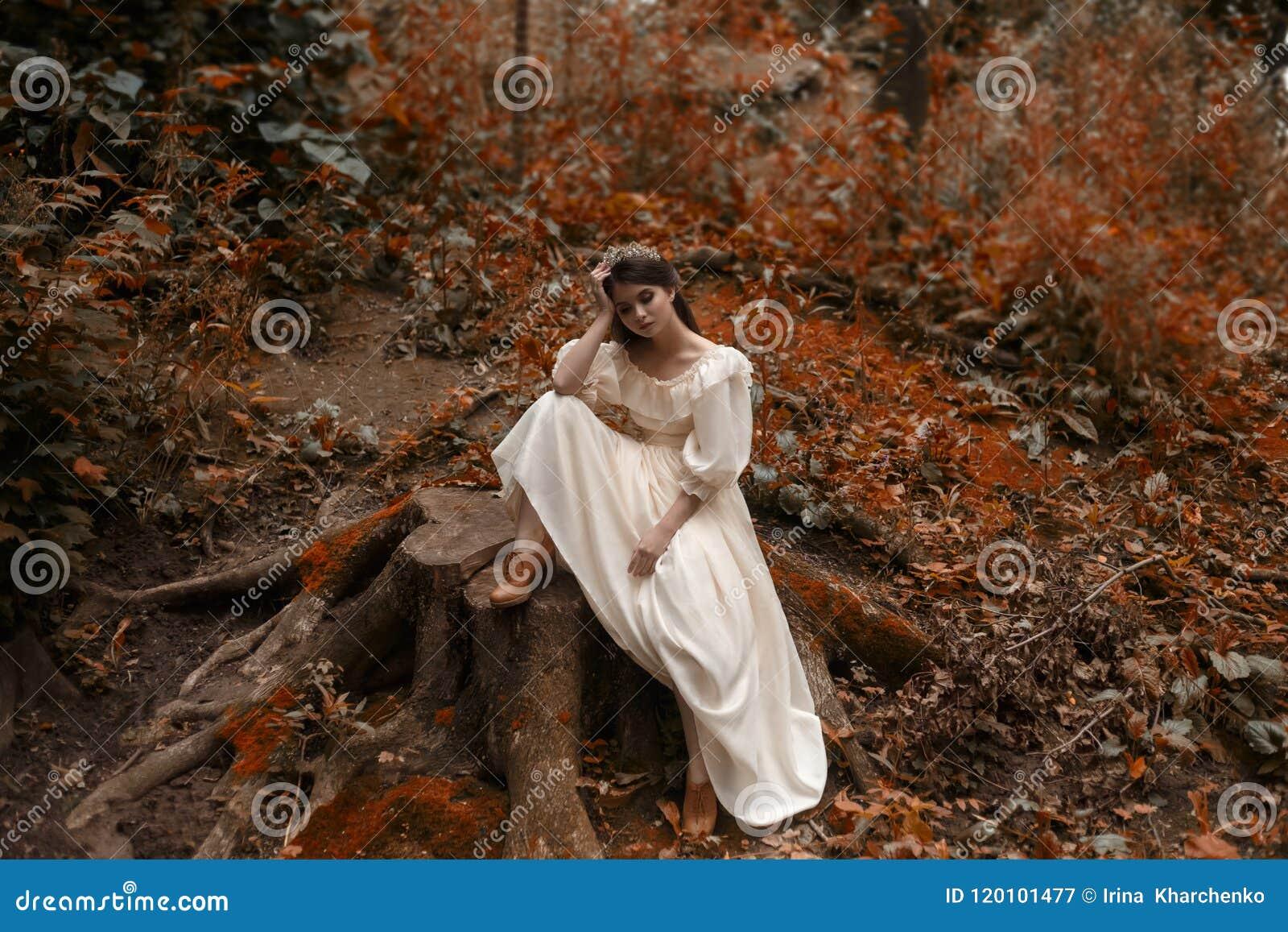 年轻人,有非常长的头发的一位公主坐一个大树桩从时髦盖子  残酷等待奇迹