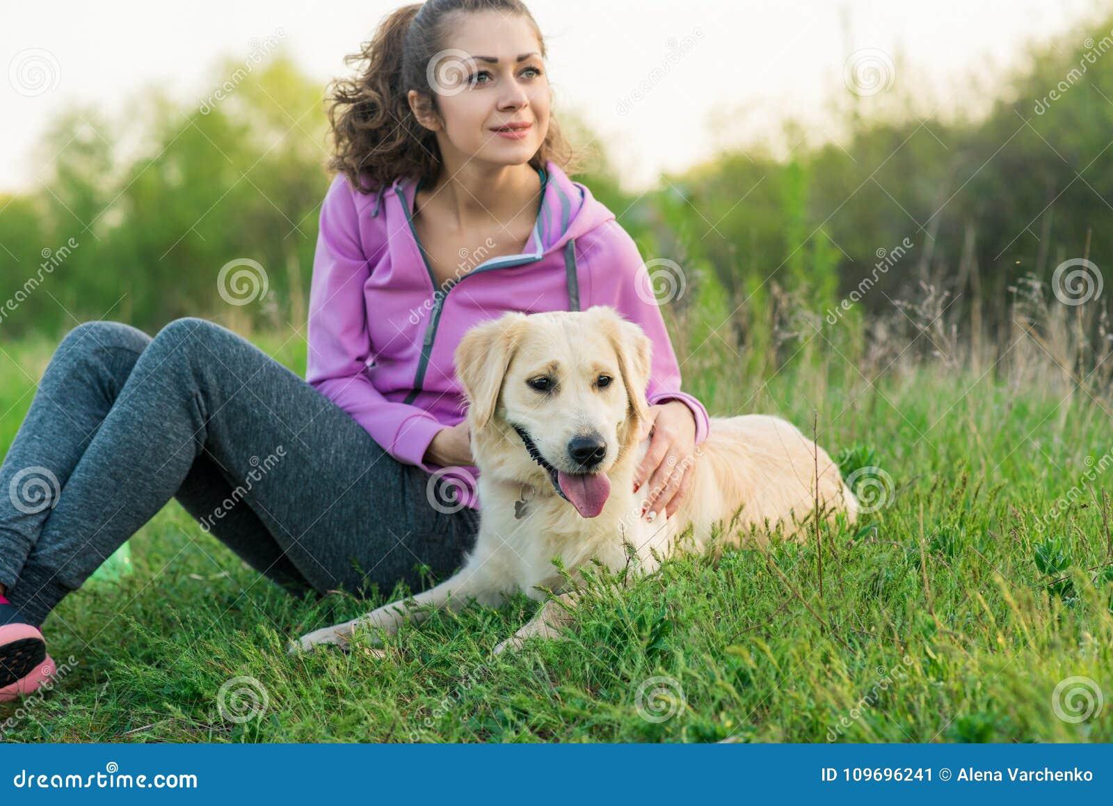 年轻俏丽女孩跑室外在春天有狗的