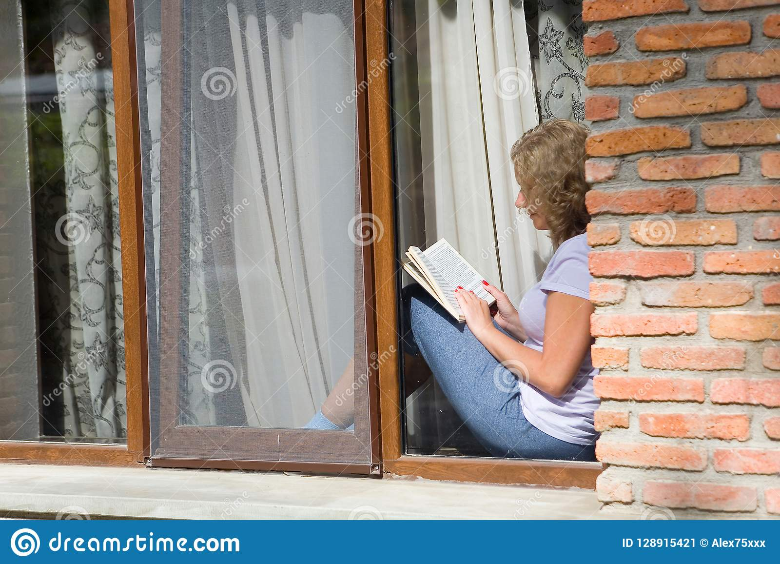 年轻俏丽的妇女坐窗台并且读书