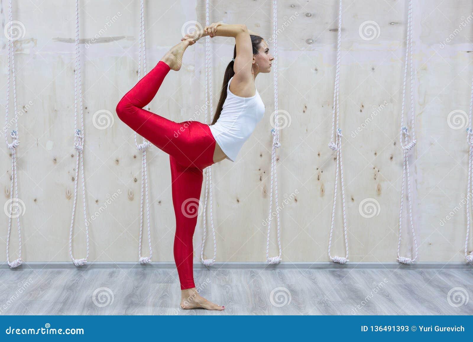 年轻信奉瑜伽者可爱的女子实践的瑜伽概念,站立在Natarajasana锻炼