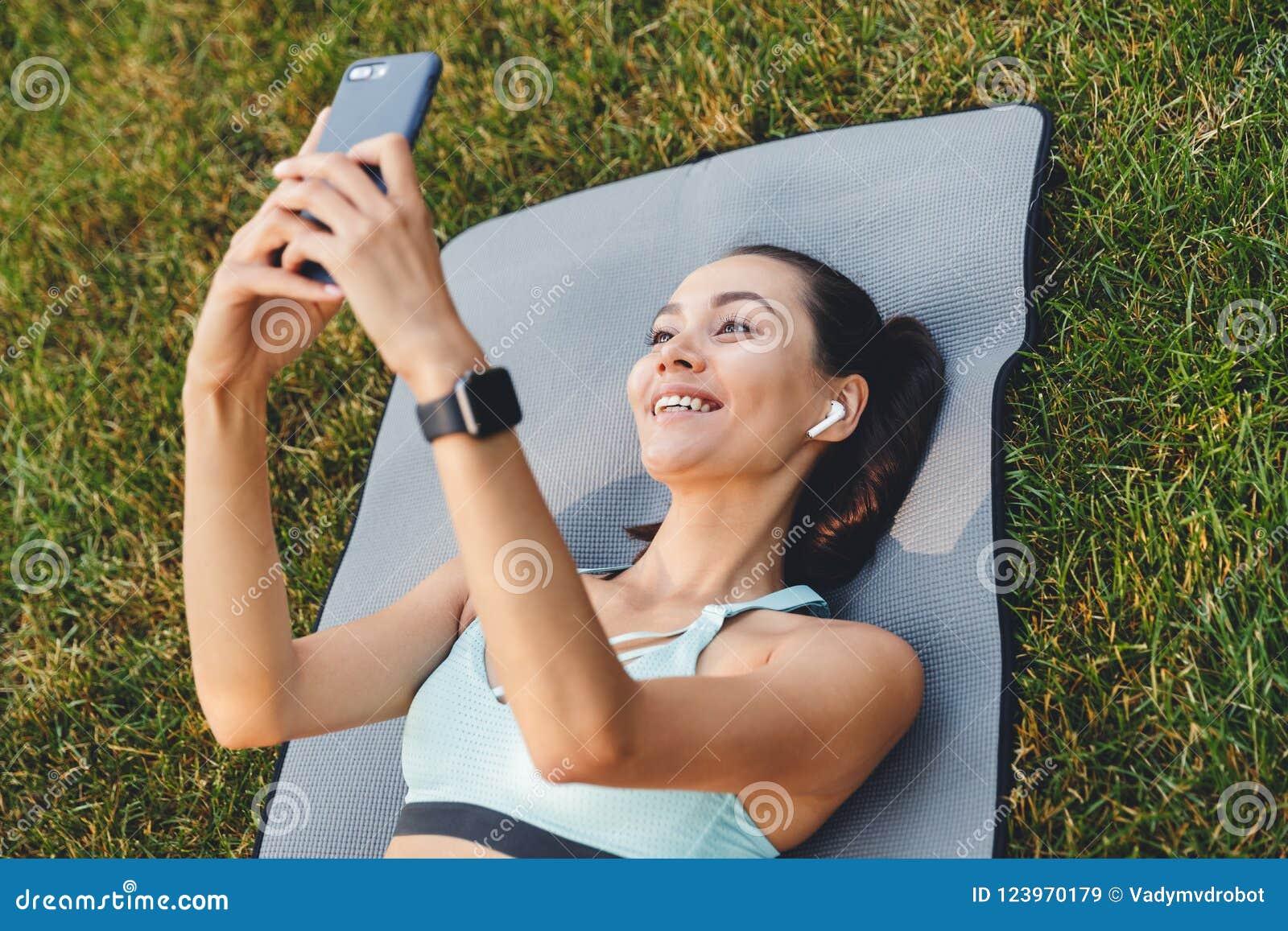 年轻健身妇女20s照片说谎在锻炼的运动服的