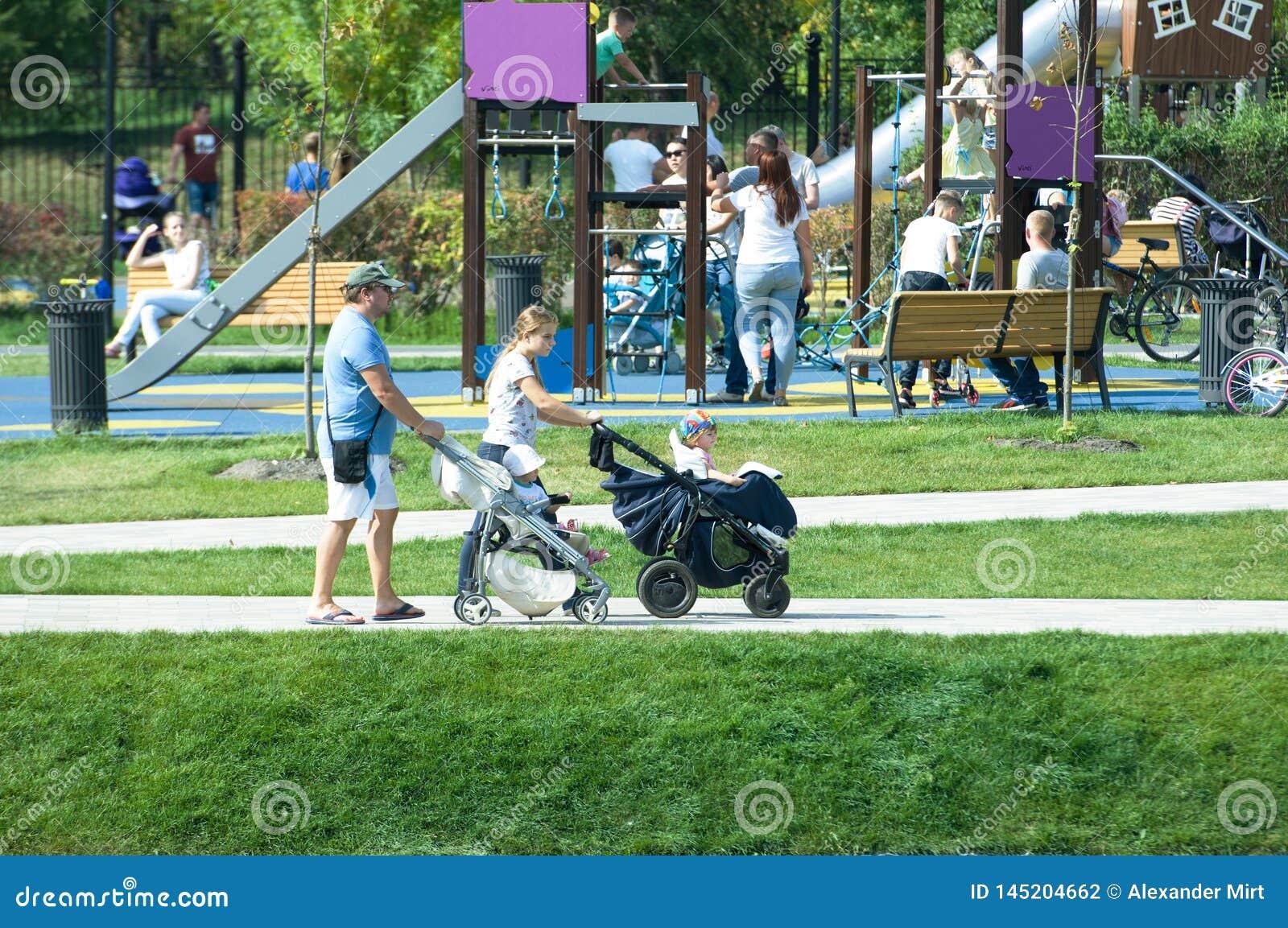 年轻加上走在Butovo公园,莫斯科,俄罗斯的孩子婴儿推车