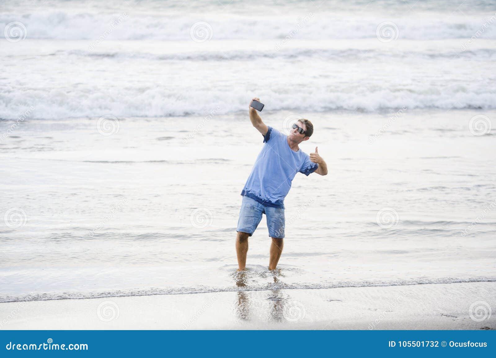 年轻可爱和愉快的白种人30s人获得乐趣在拍与手机微笑的亚洲海滩selfie照片激动