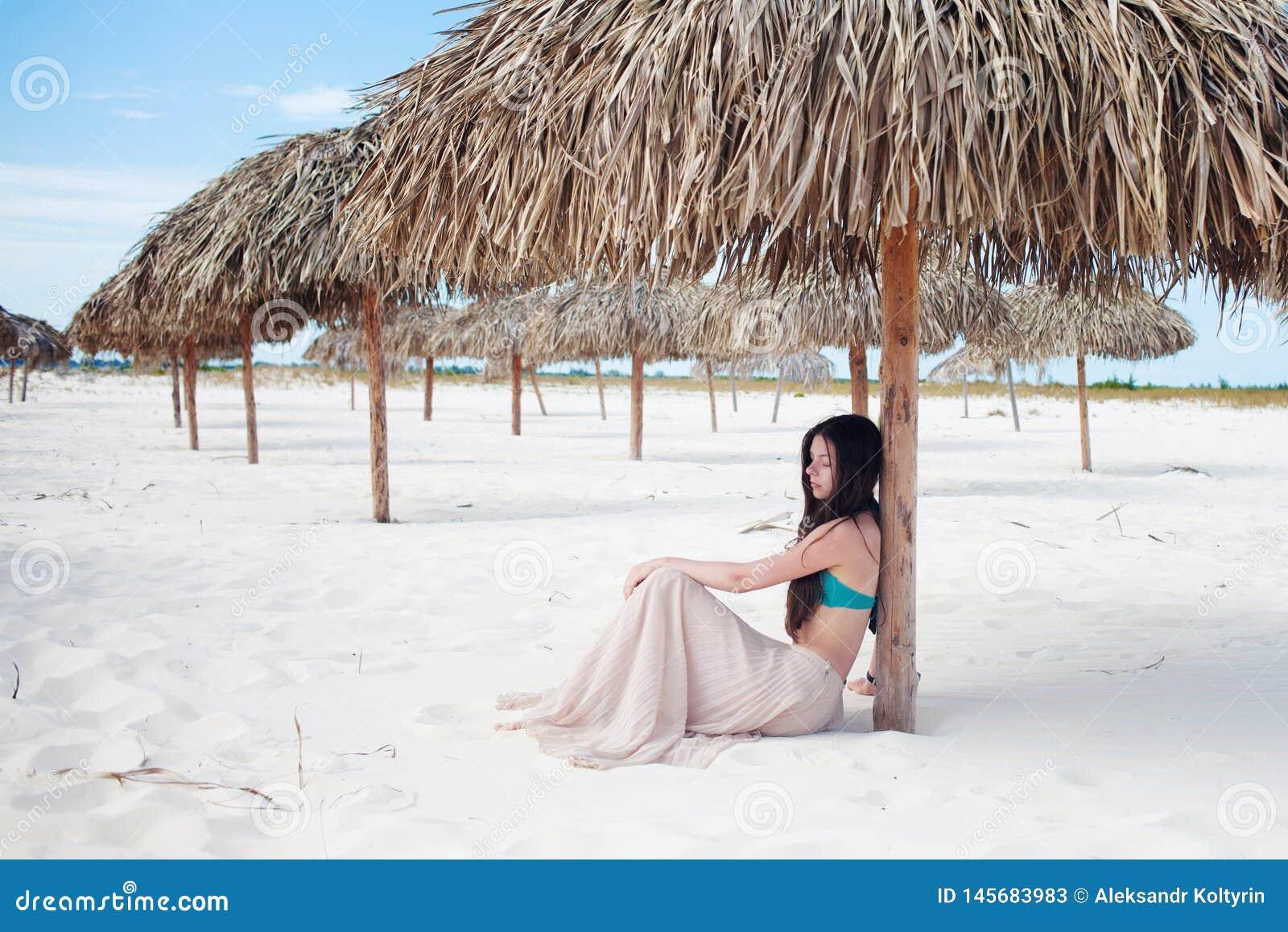 年轻可爱的妇女在度假在海的,坐沙子在秸杆伞下