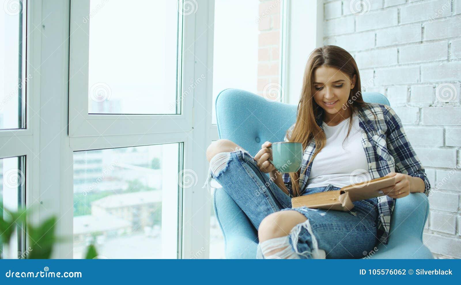 年轻可爱的妇女读了书并且喝咖啡坐现代顶楼公寓的阳台