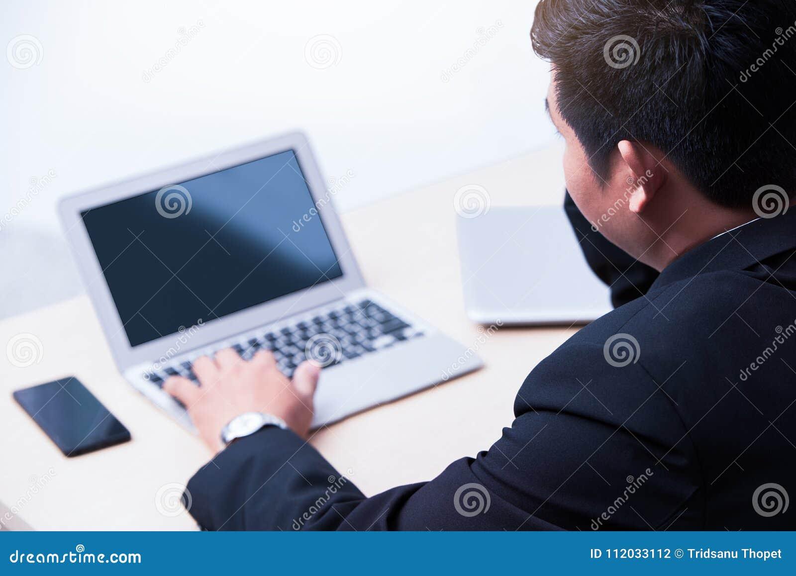 年轻商人键入的膝上型计算机
