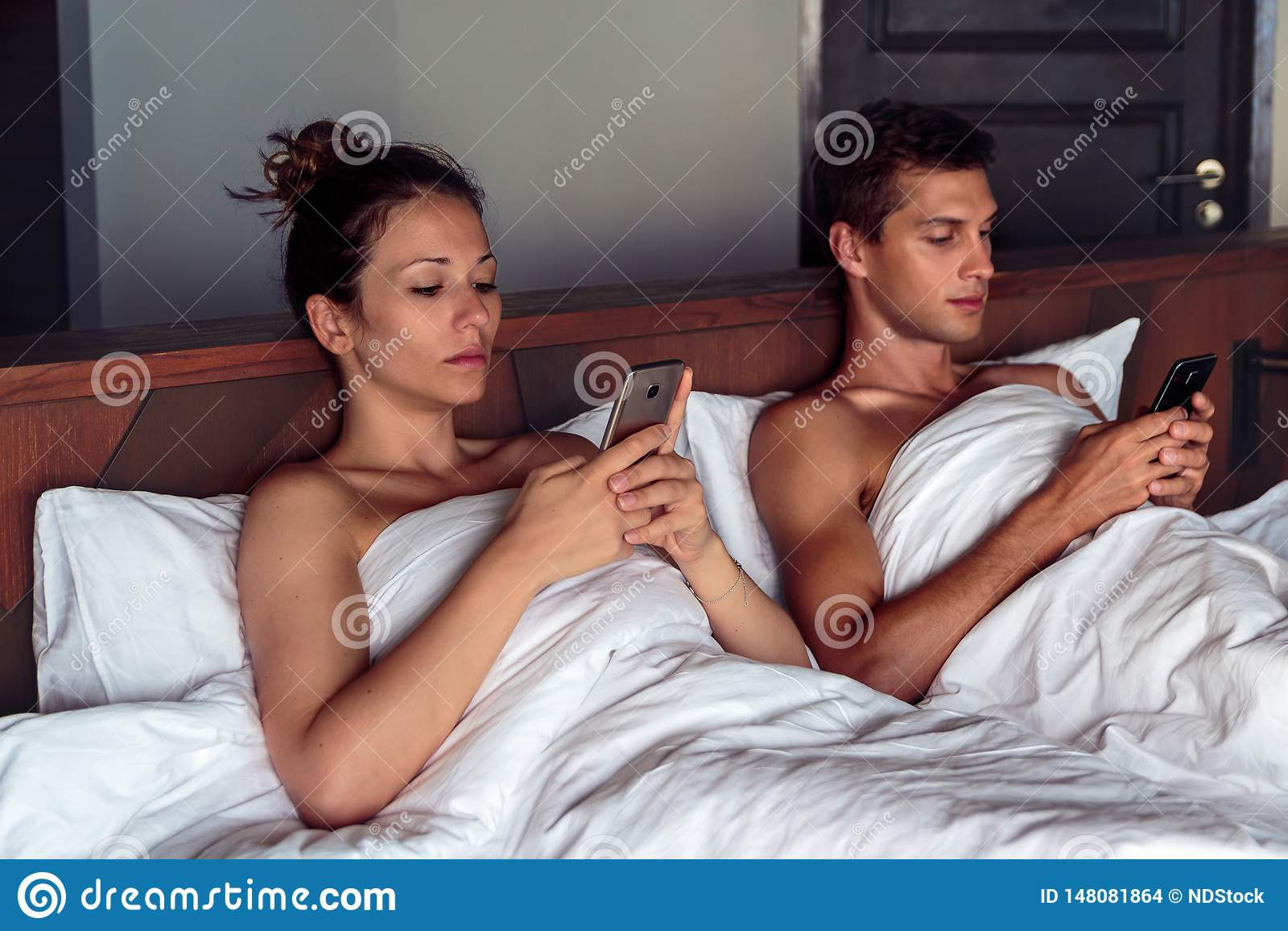 年轻夫妇在使用他们的忽略的智能手机的床上