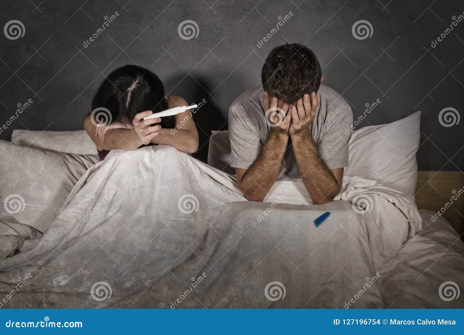 年轻夫妇在妊娠试验的正面结果以后被惊吓和被注重的床上与期待不需要的婴孩和ma的孕妇