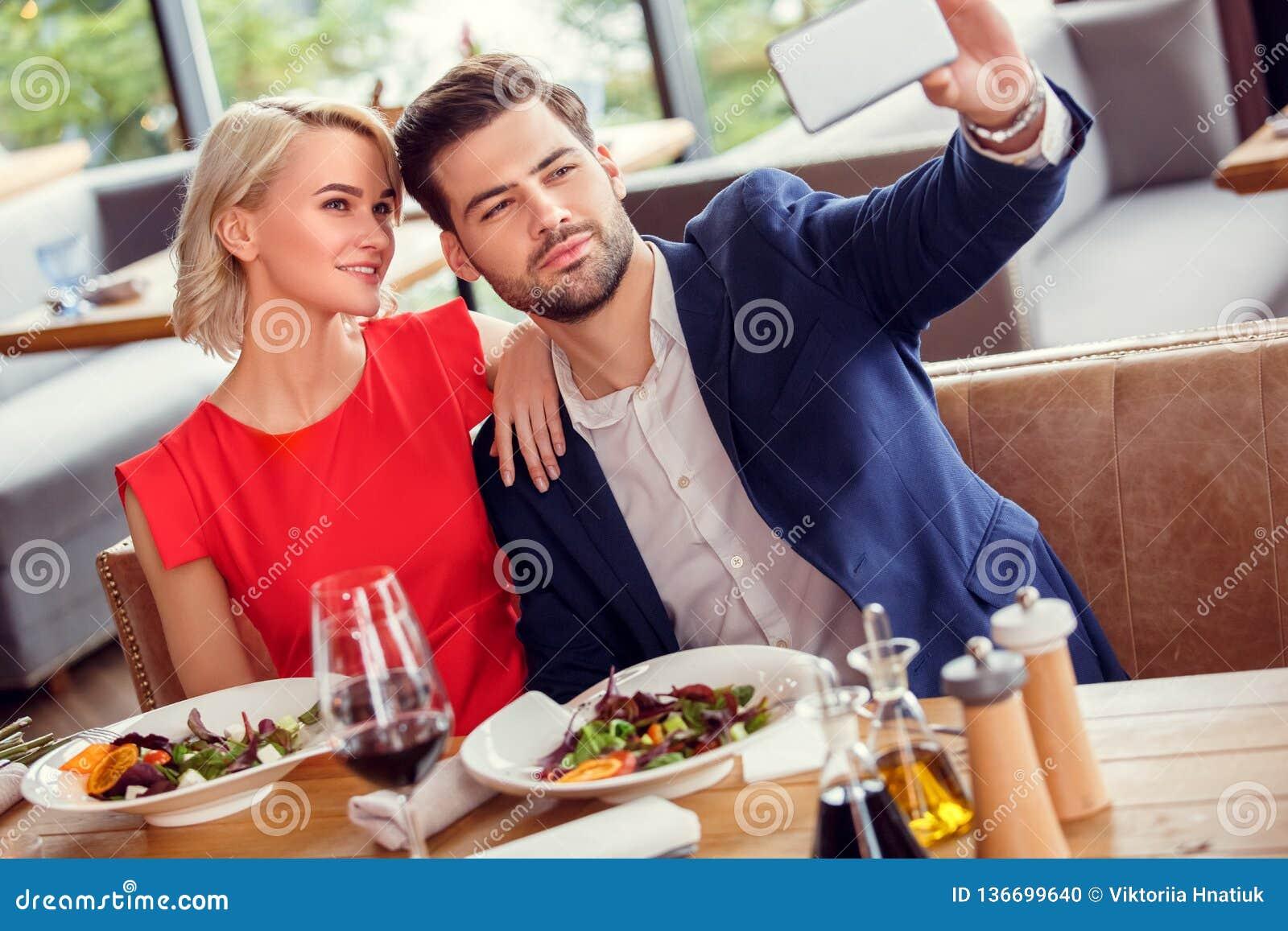 年轻夫妇在餐馆坐的用餐的日期拿着采取selfie照片摆在的智能手机快乐