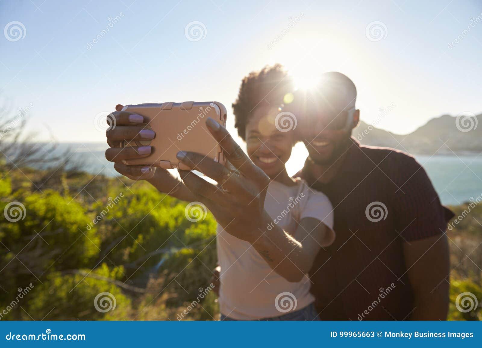 年轻夫妇姿势为在Clifftop的假日Selfie