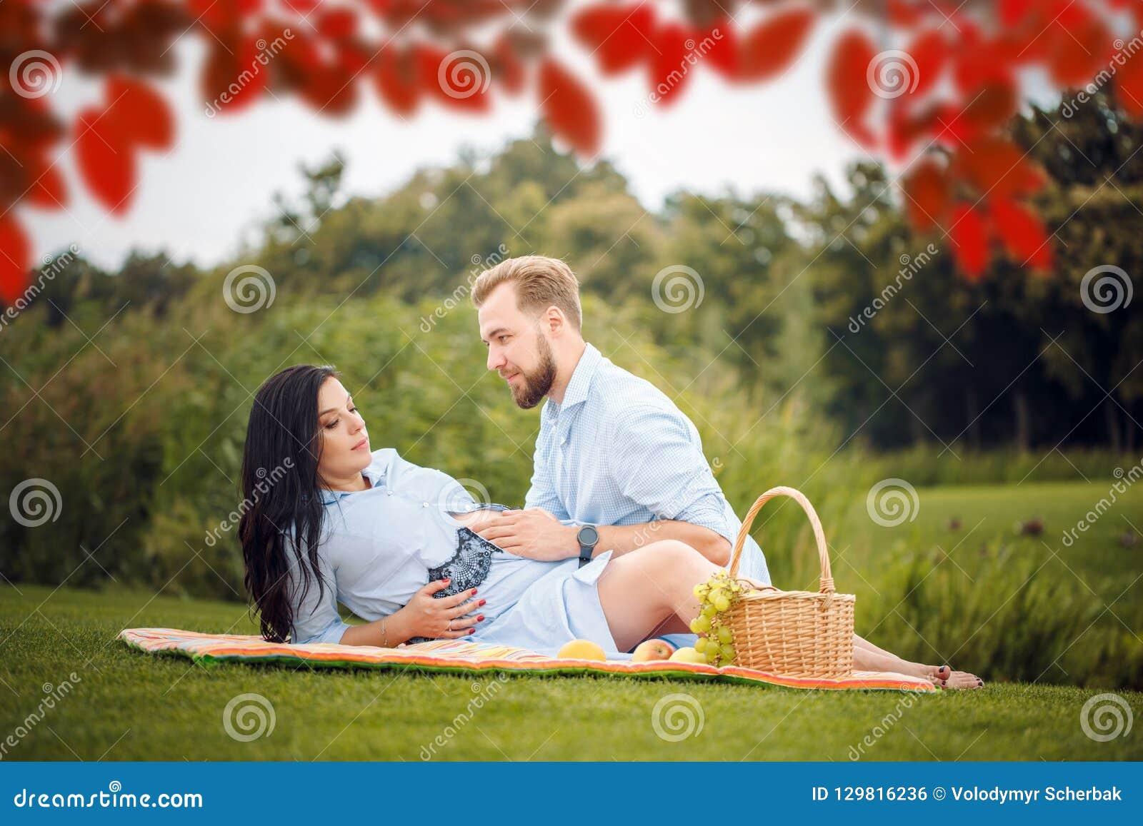 年轻夫妇有野餐在城市公园,妇女期待一个婴孩