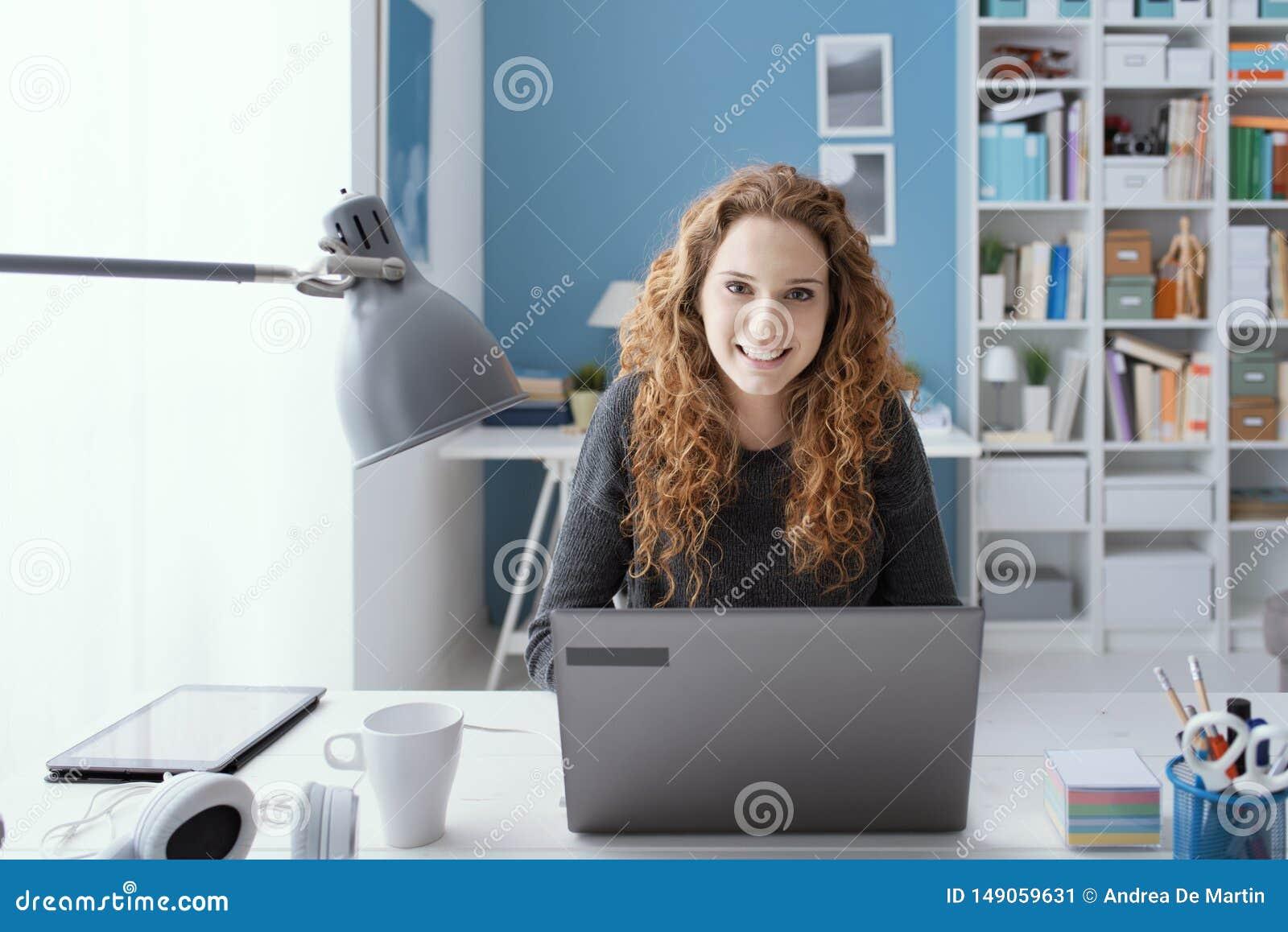 年轻女人与她的膝上型计算机一起使用