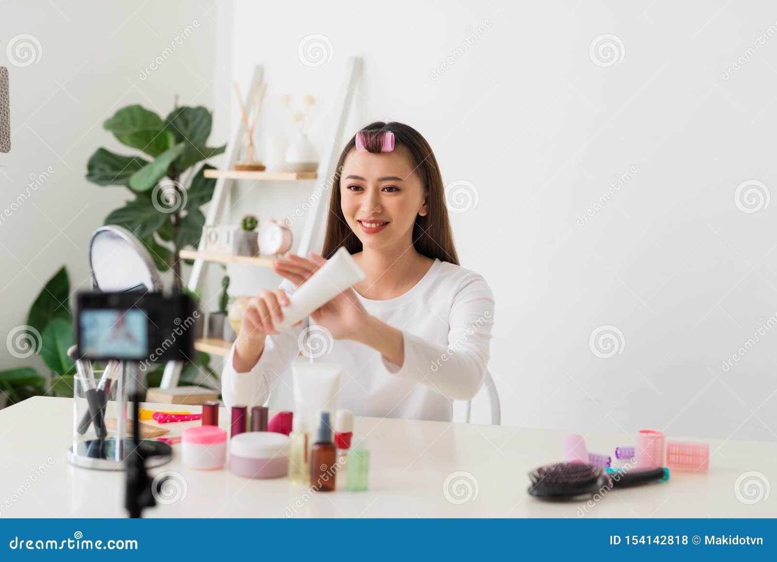 年轻女人专业秀丽vlogger或博客作者录音化妆构成讲解与分享的照相机在社会媒介