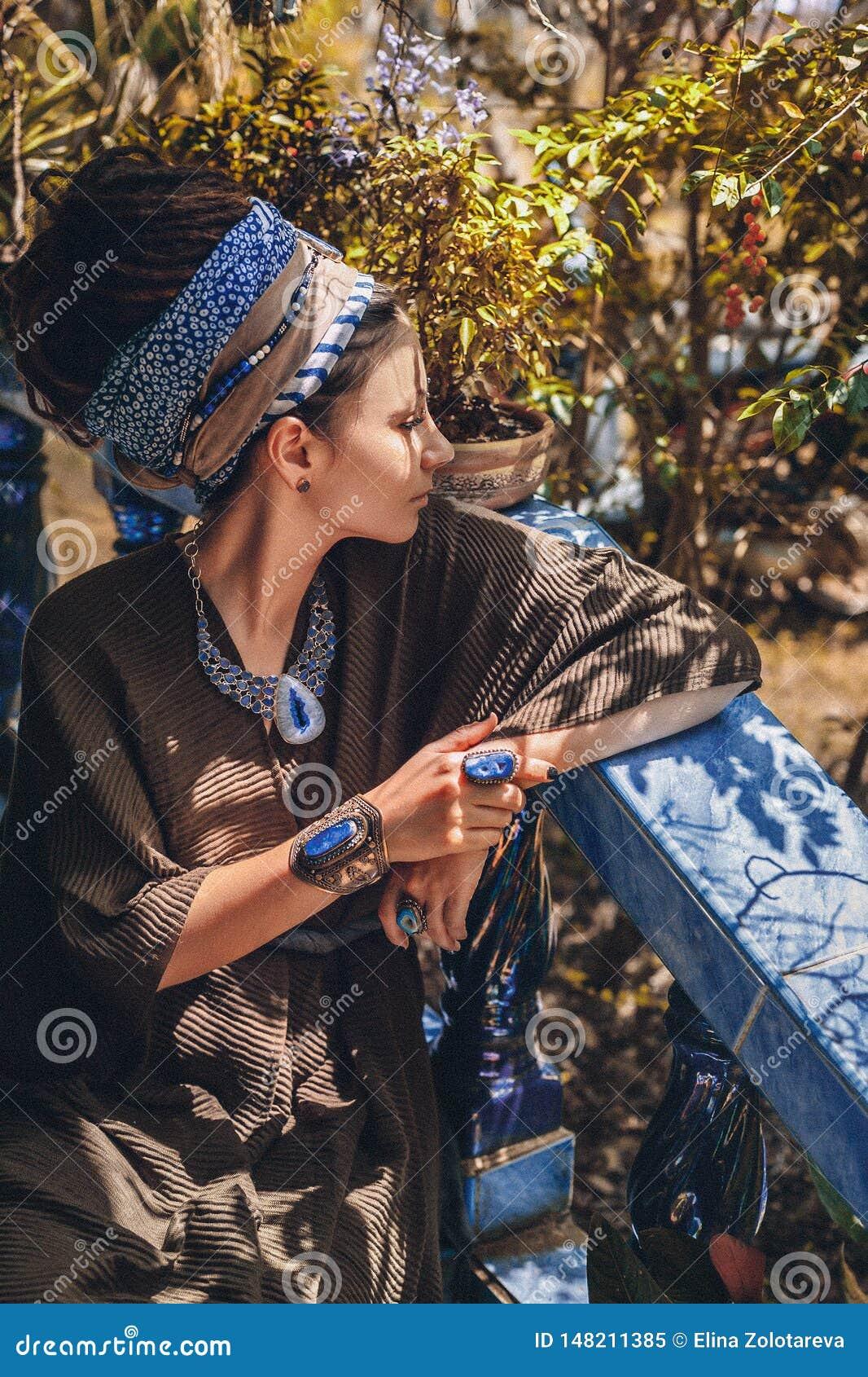 年轻女人佩带的宝石首饰接近的画象户外