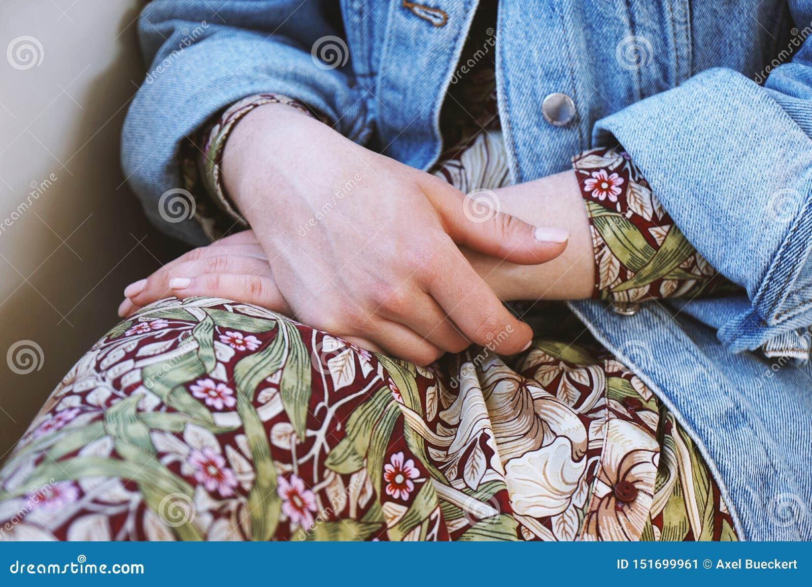 年轻女人佩带的牛仔布夹克的中间部分在夏天礼服的有花卉样式的