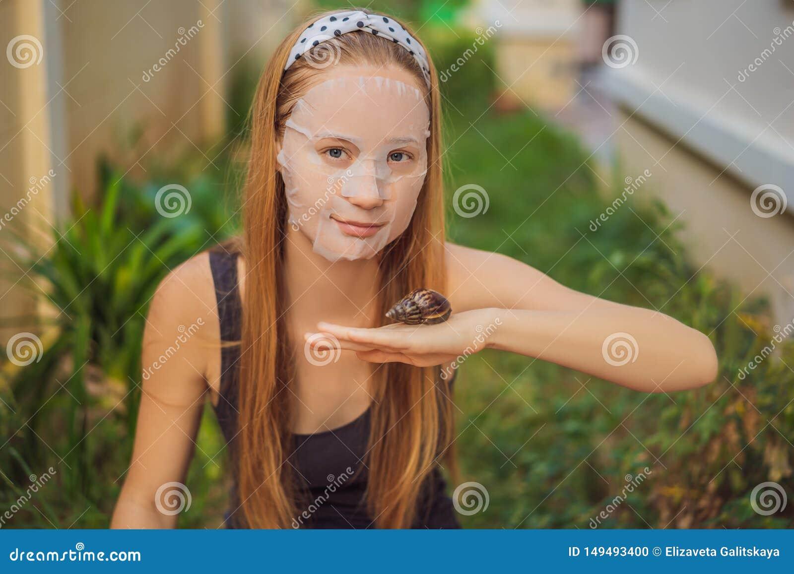 年轻女人做与蜗牛黏液的一面膜 爬行在面膜的蜗牛