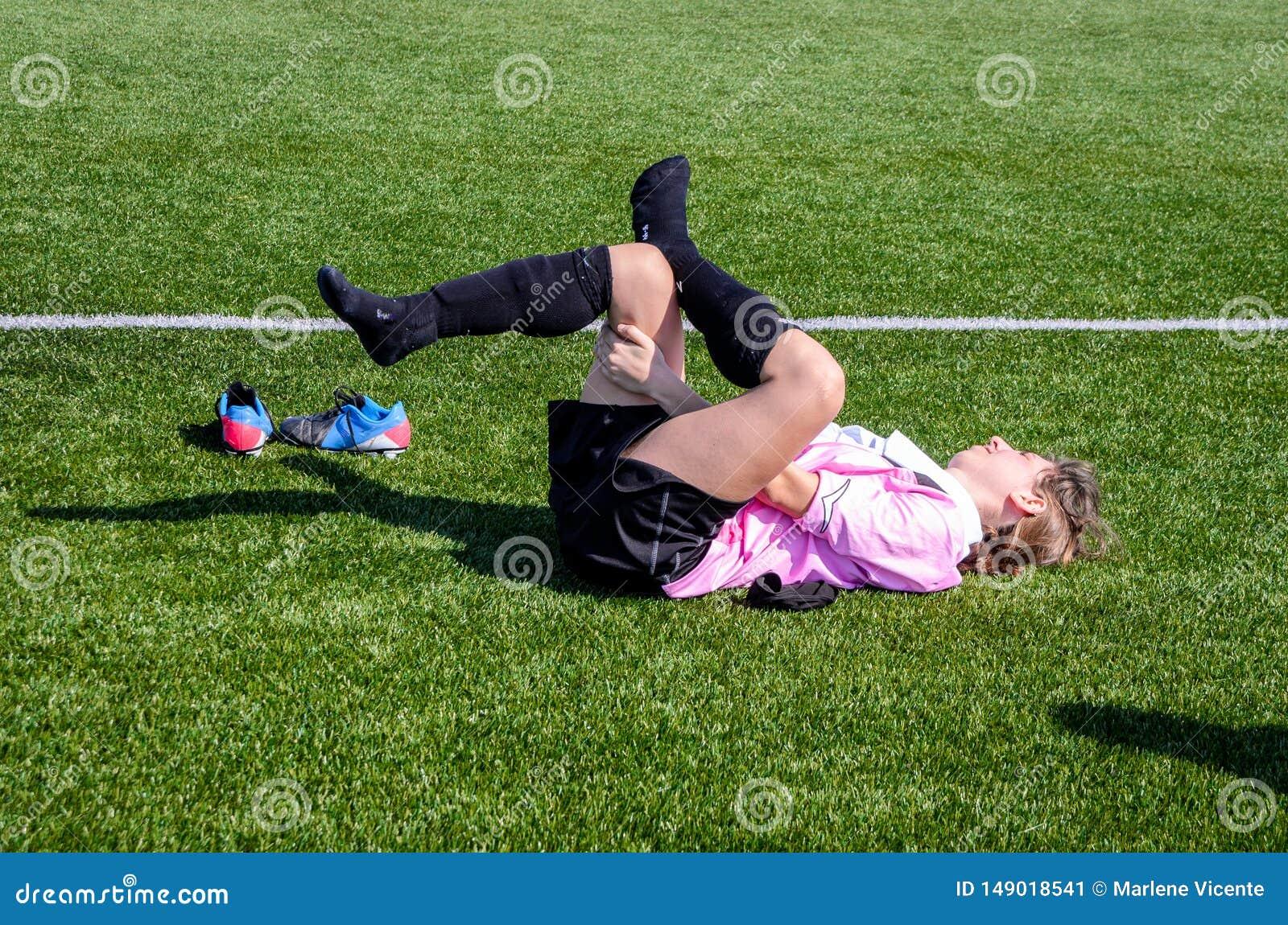 年轻女人做舒展在足球比赛以后