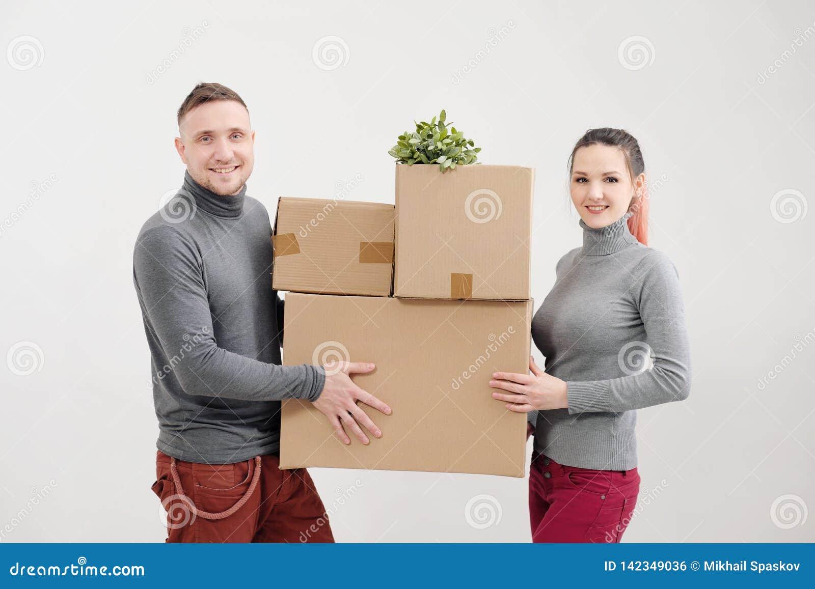年轻女人和一个人运载有事的重的纸板箱 白光公寓 他们笑并且亲吻