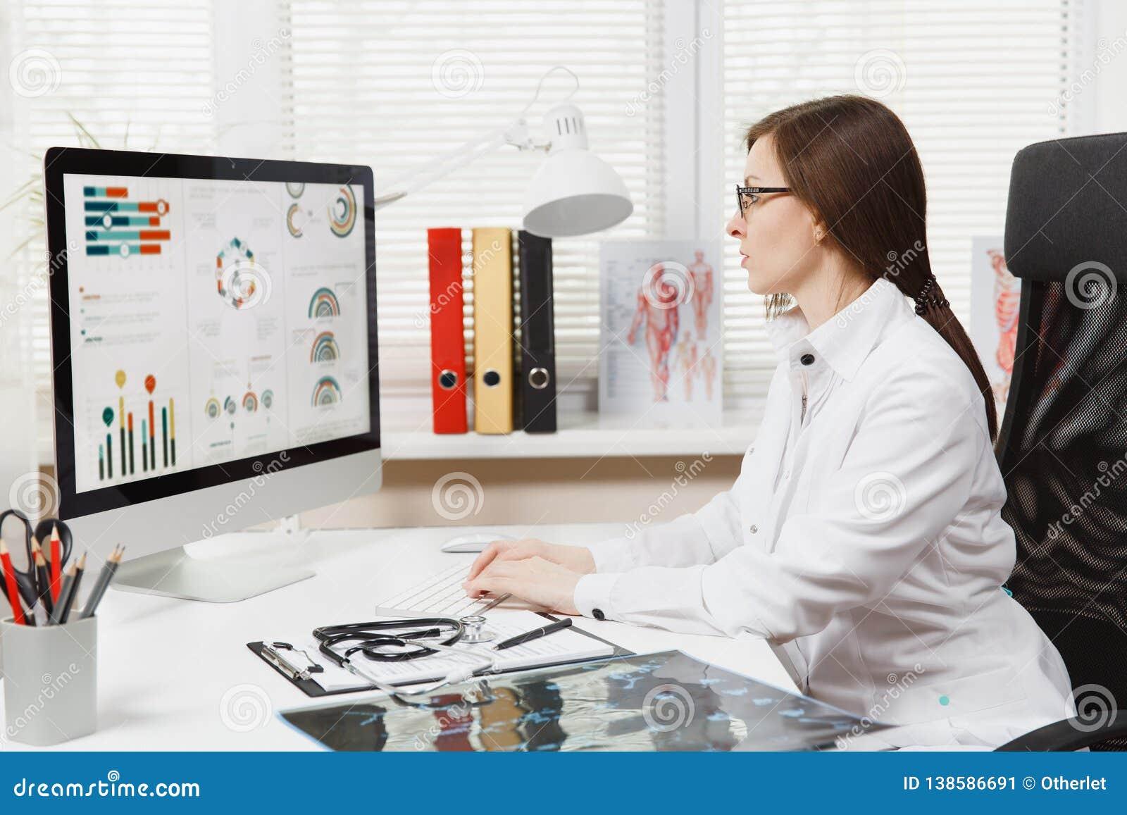 年轻女人在书桌,运转坐有医疗文件的现代计算机在轻的办公室在医院 女性