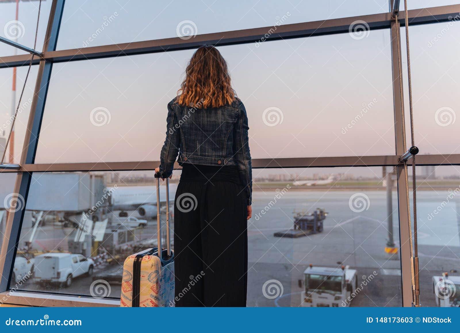 年轻女人在看飞机的机场在离开前