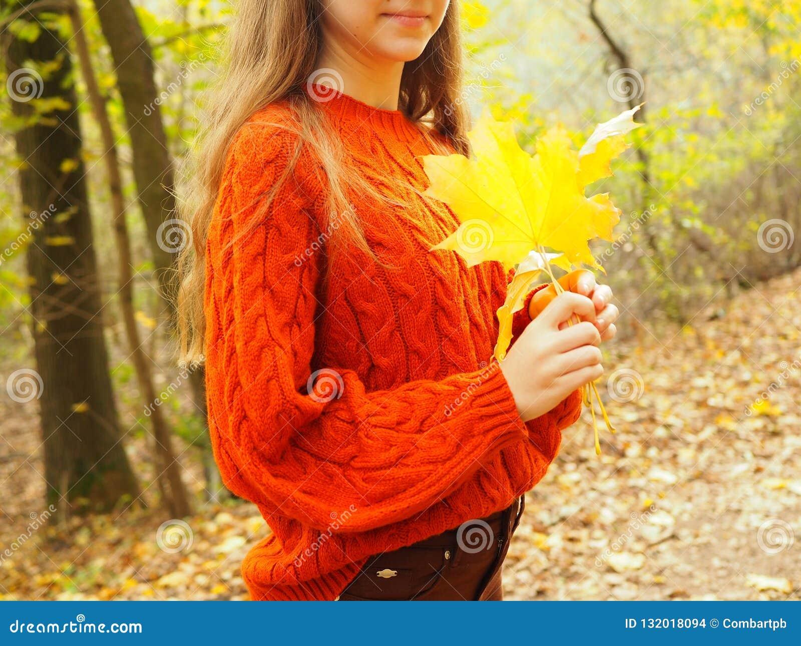 年轻女人在秋天公园,有黄色叶子的少年
