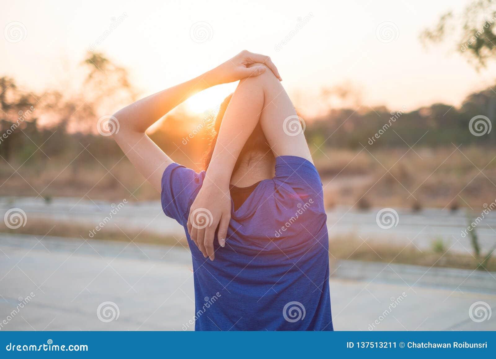 年轻女人在行使前行使在公园 她舒展了她的体检的胳膊有太阳的背景