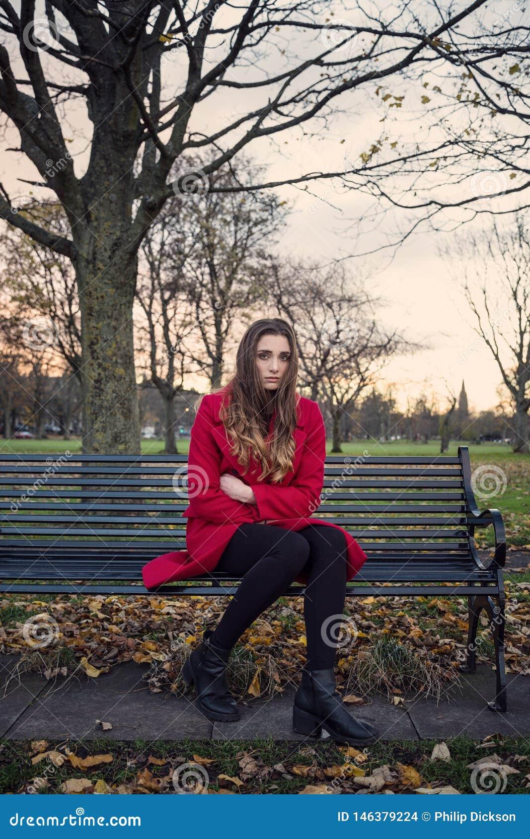 年轻女人坐不快乐公园长椅的感觉