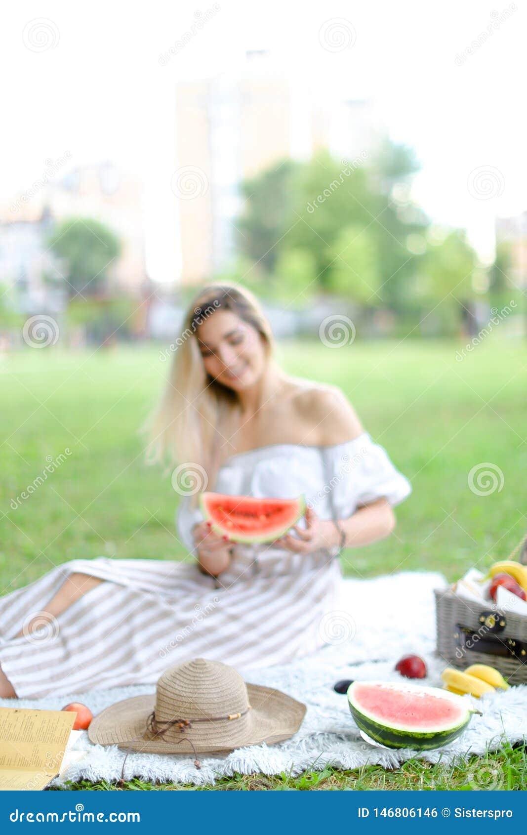 年轻女人坐格子花呢披肩在果子和帽子附近,吃西瓜,草在背景中