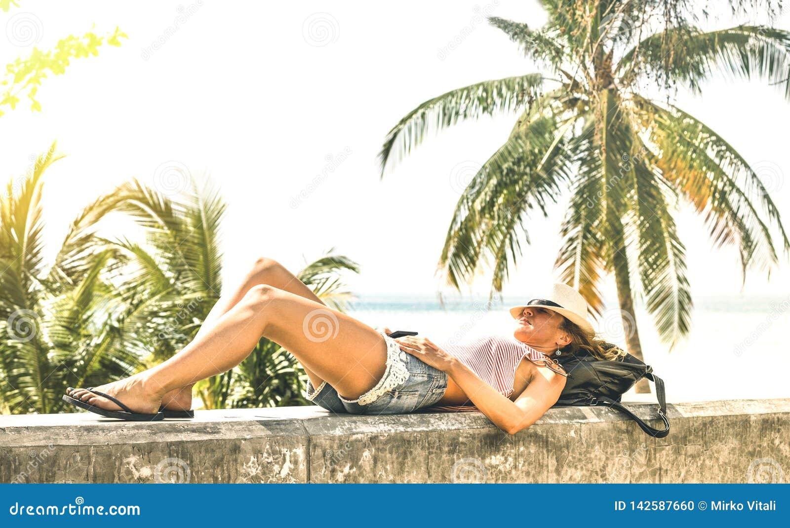 年轻女人放松在石墙上的旅行influencer在普吉岛海滩散步-旅行癖与冒险女孩的假期概念
