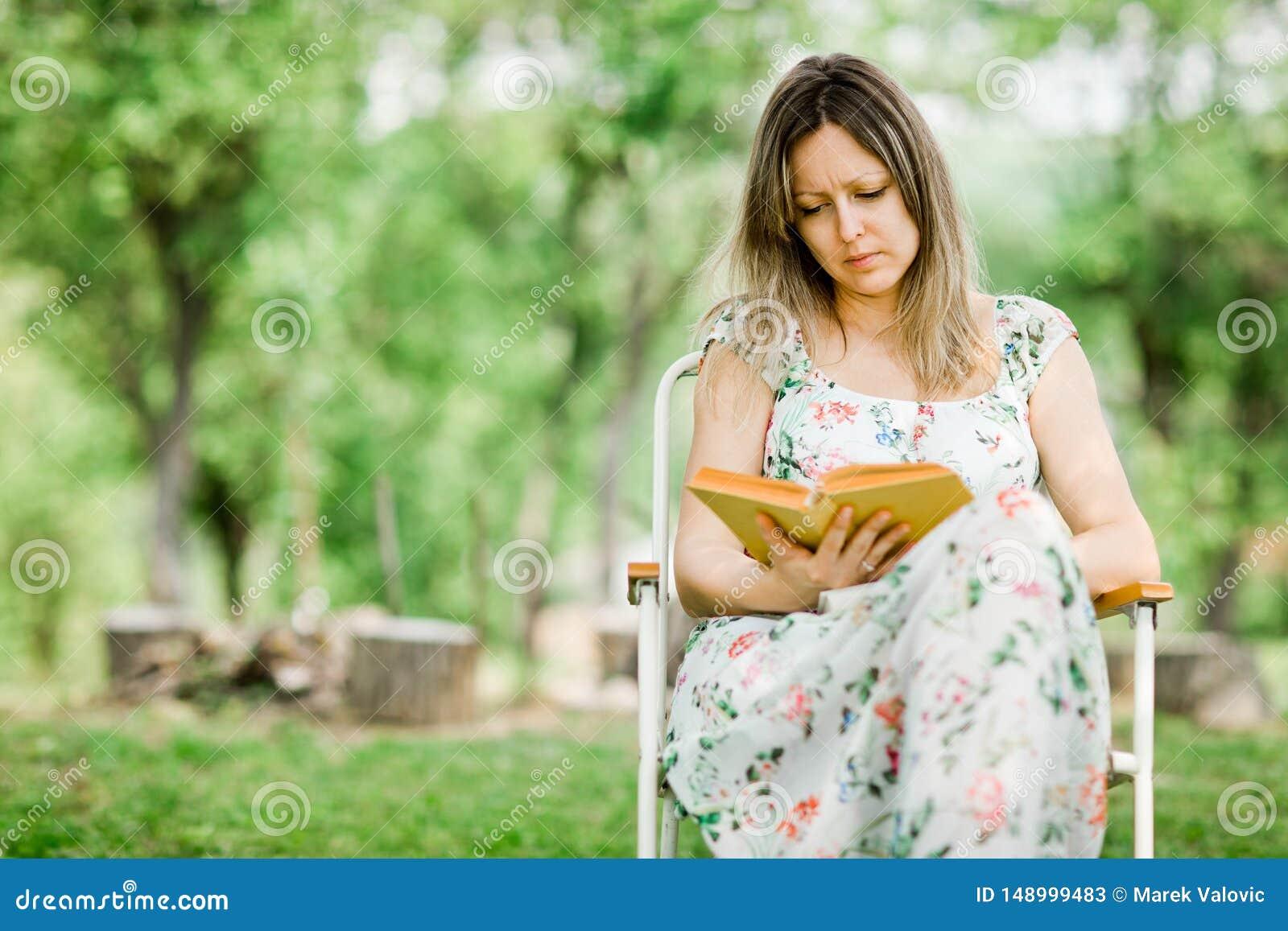 年轻女人是看书室外在庭院里