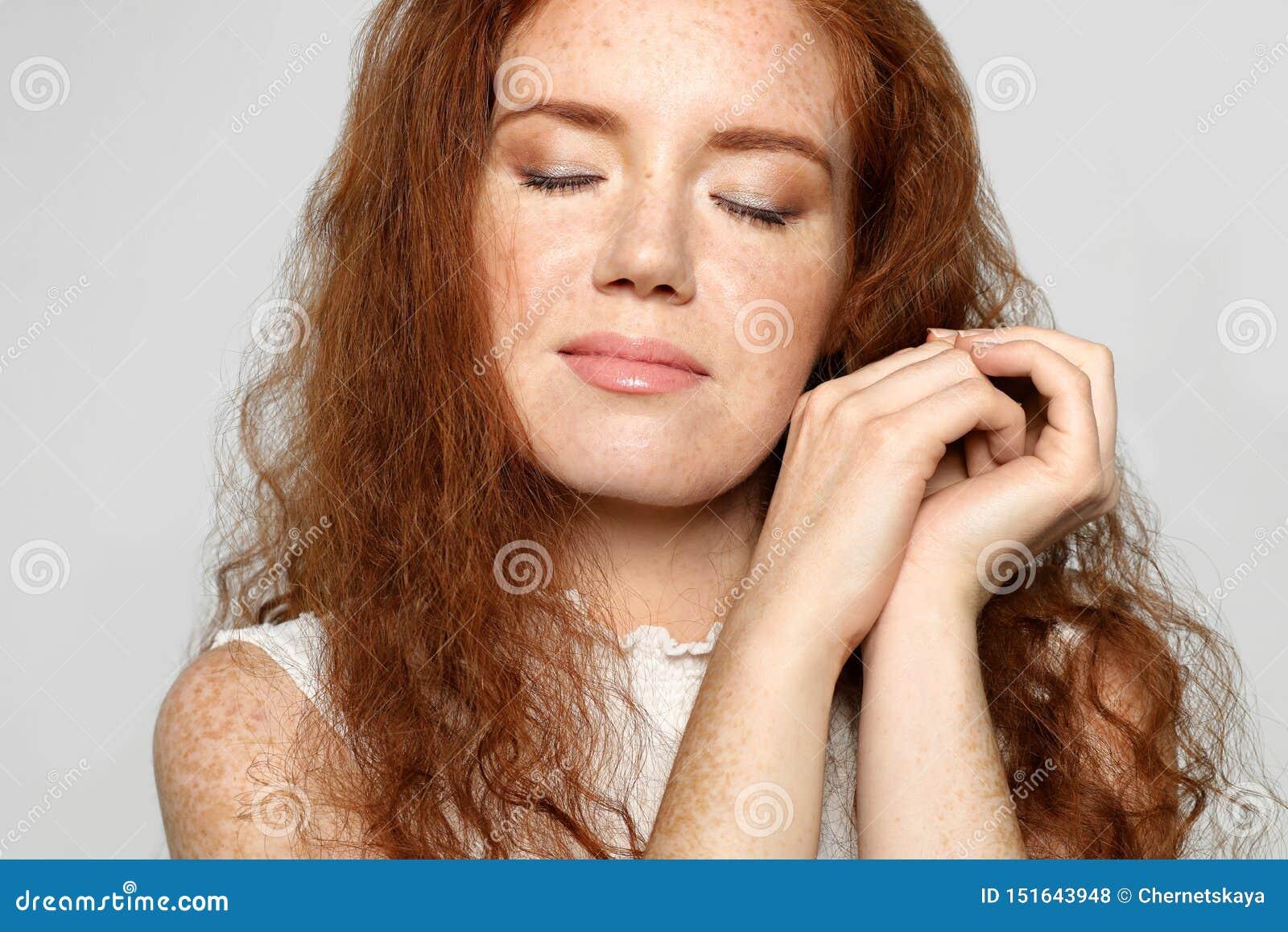 年轻女人画象有脸蛋漂亮的在灰色背景