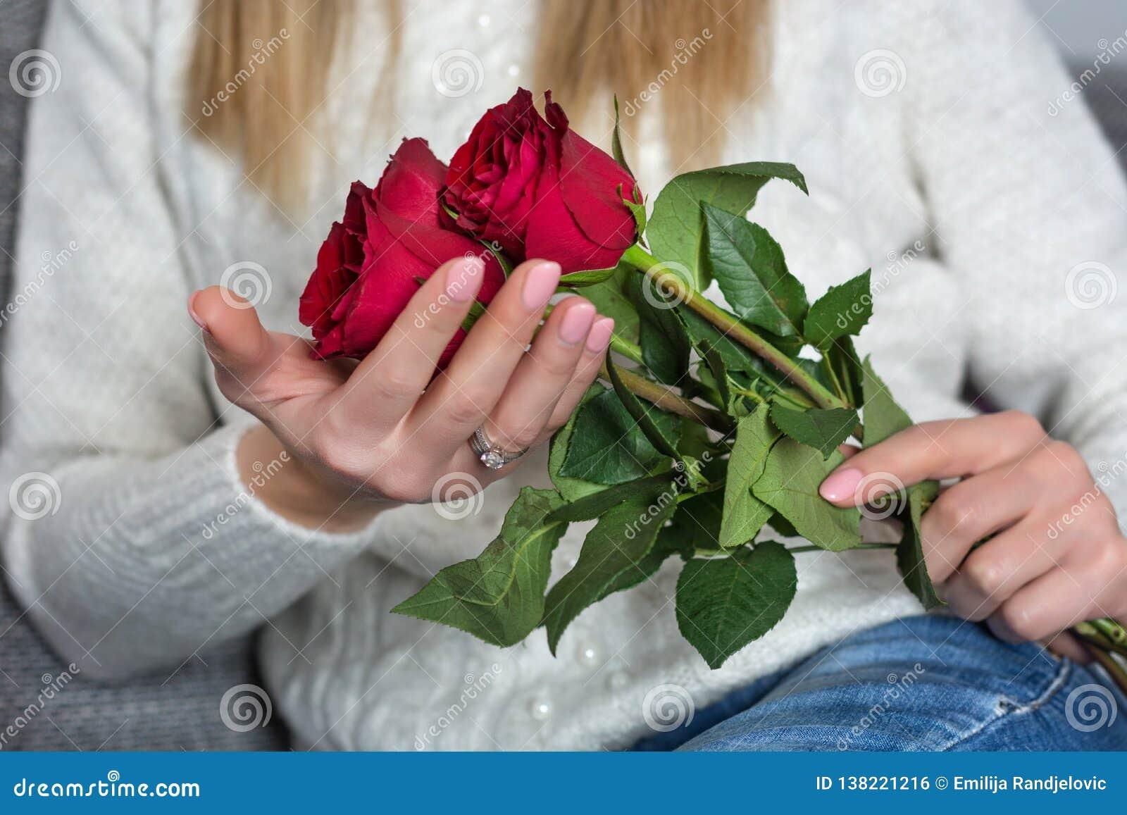 年轻女人藏品美好的红色在手和在家坐上上升了在床上