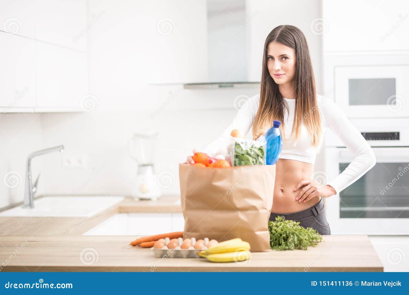 年轻女人身分在有购买的厨房里在桌上