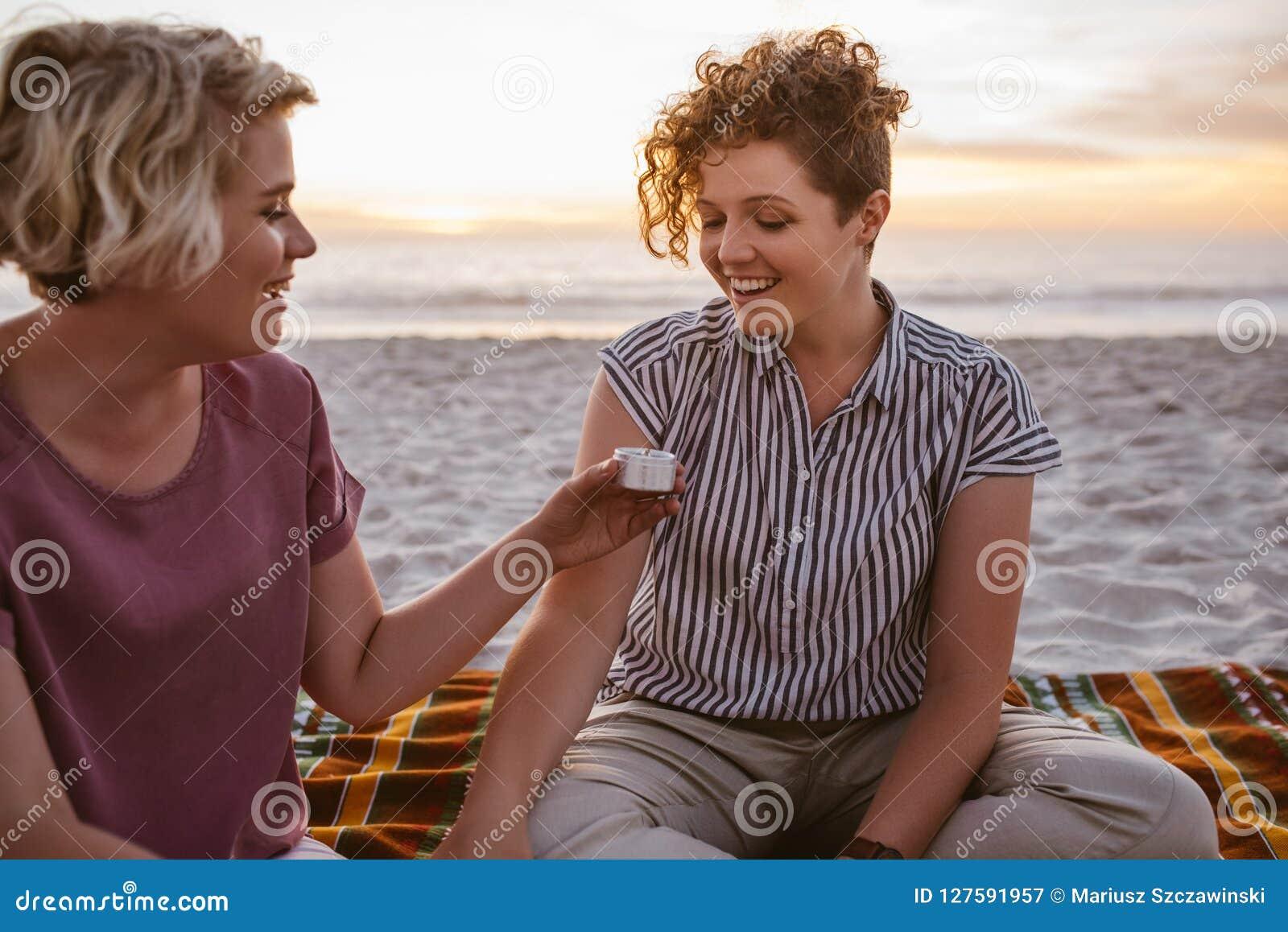 年轻女同性恋的夫妇坐海滩毯子在黄昏