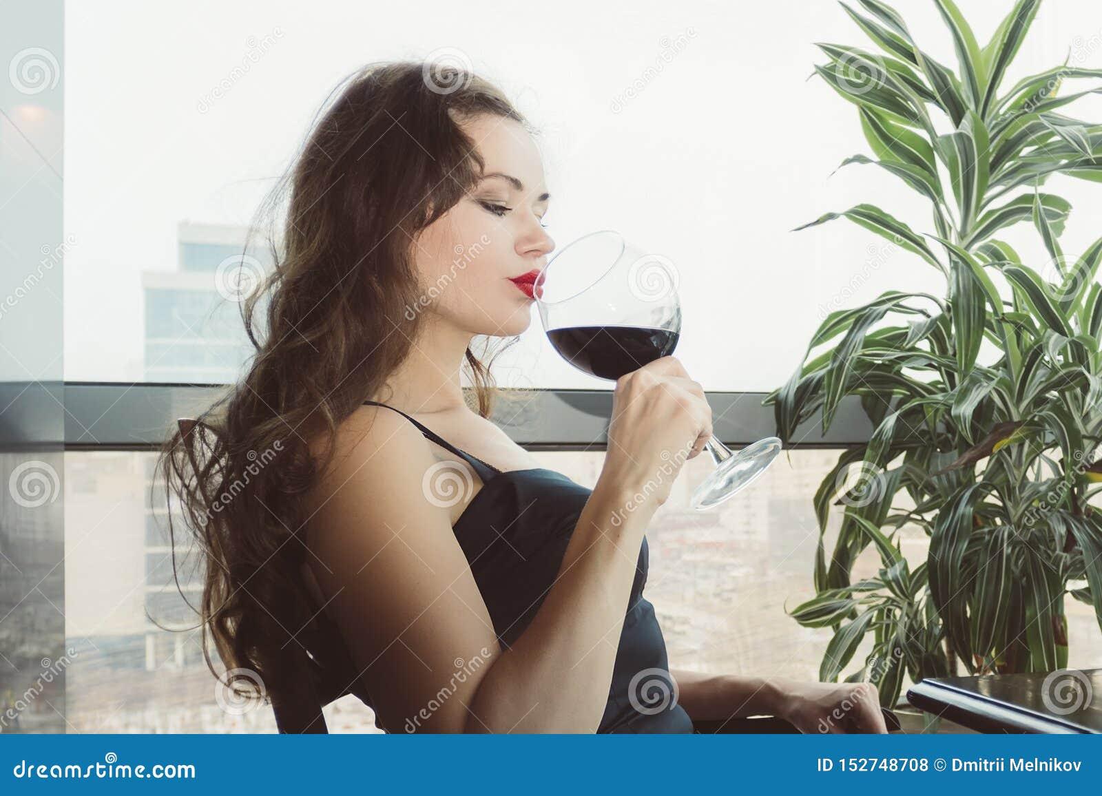 年轻女性与眼睛的顾客饮用的红酒特写镜头画象关闭了 妇女饮用的酒,采取从a的SIP