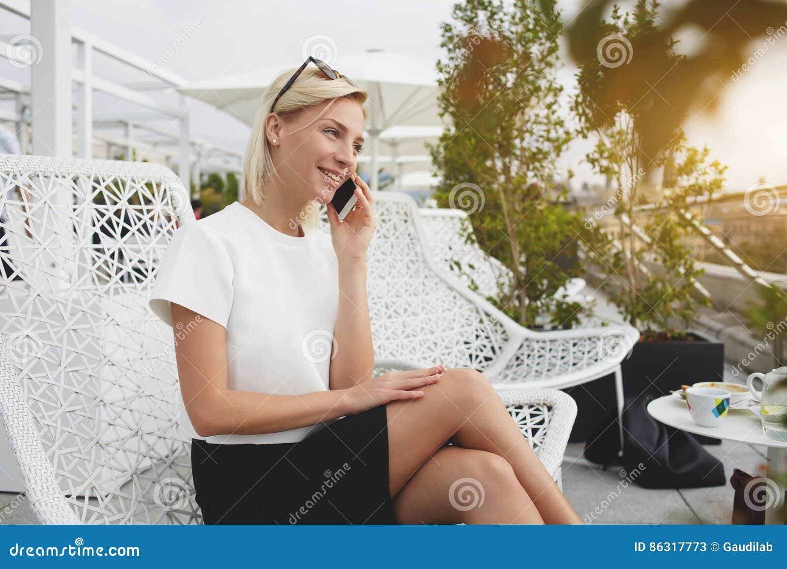 年轻女性谈话在手机,当坐户外时