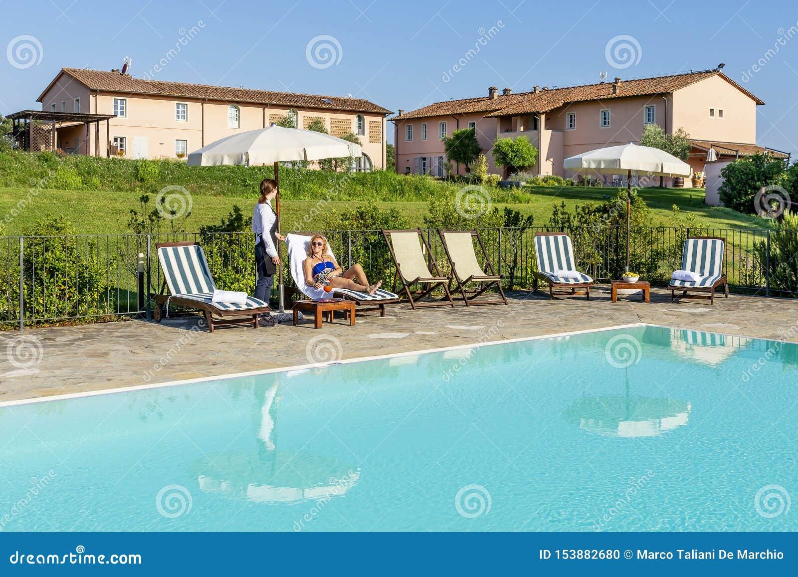 年轻女服务员服务游泳池边鸡尾酒给顾客坐在一种手段的一个懒人在比萨,意大利乡下