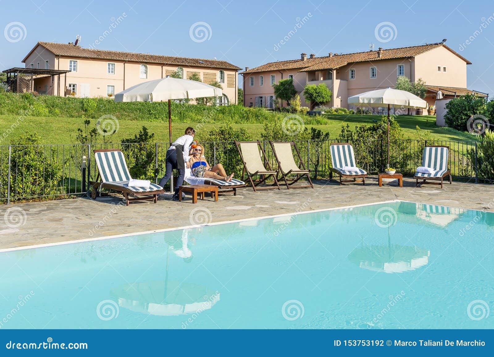 年轻女服务员服务游泳池边鸡尾酒给顾客坐在一种手段的一个懒人在比萨,托斯卡纳,Ital乡下