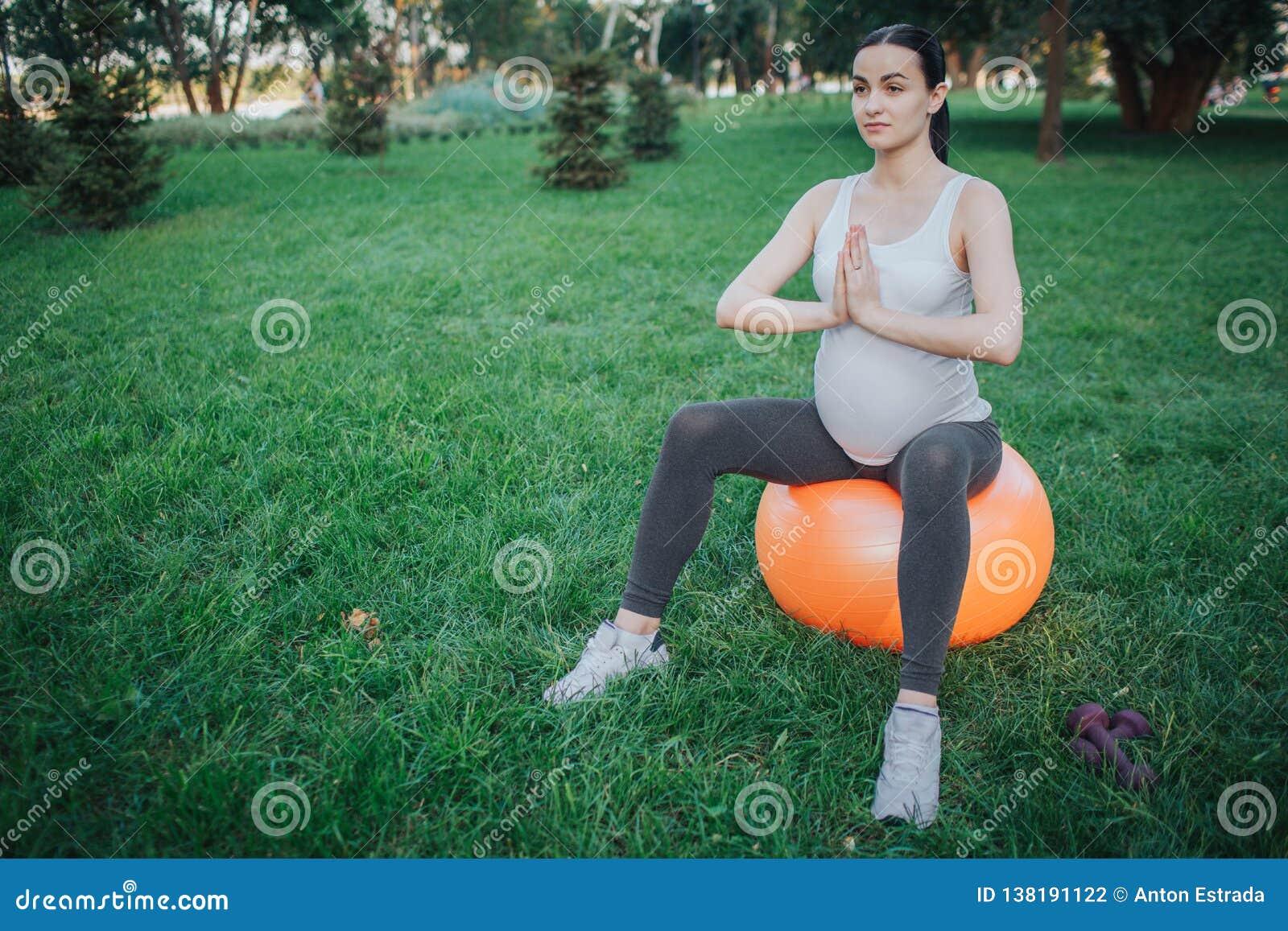 年轻孕妇坐橙色健身球在绿色公园并且思考 她在祈祷的姿势结合在一起使手