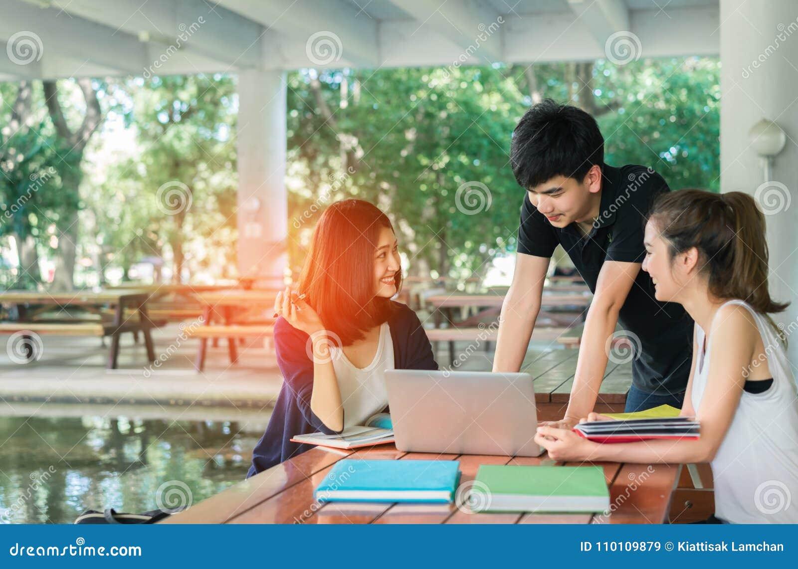 年轻学生团体与学校文件夹,膝上型计算机咨询