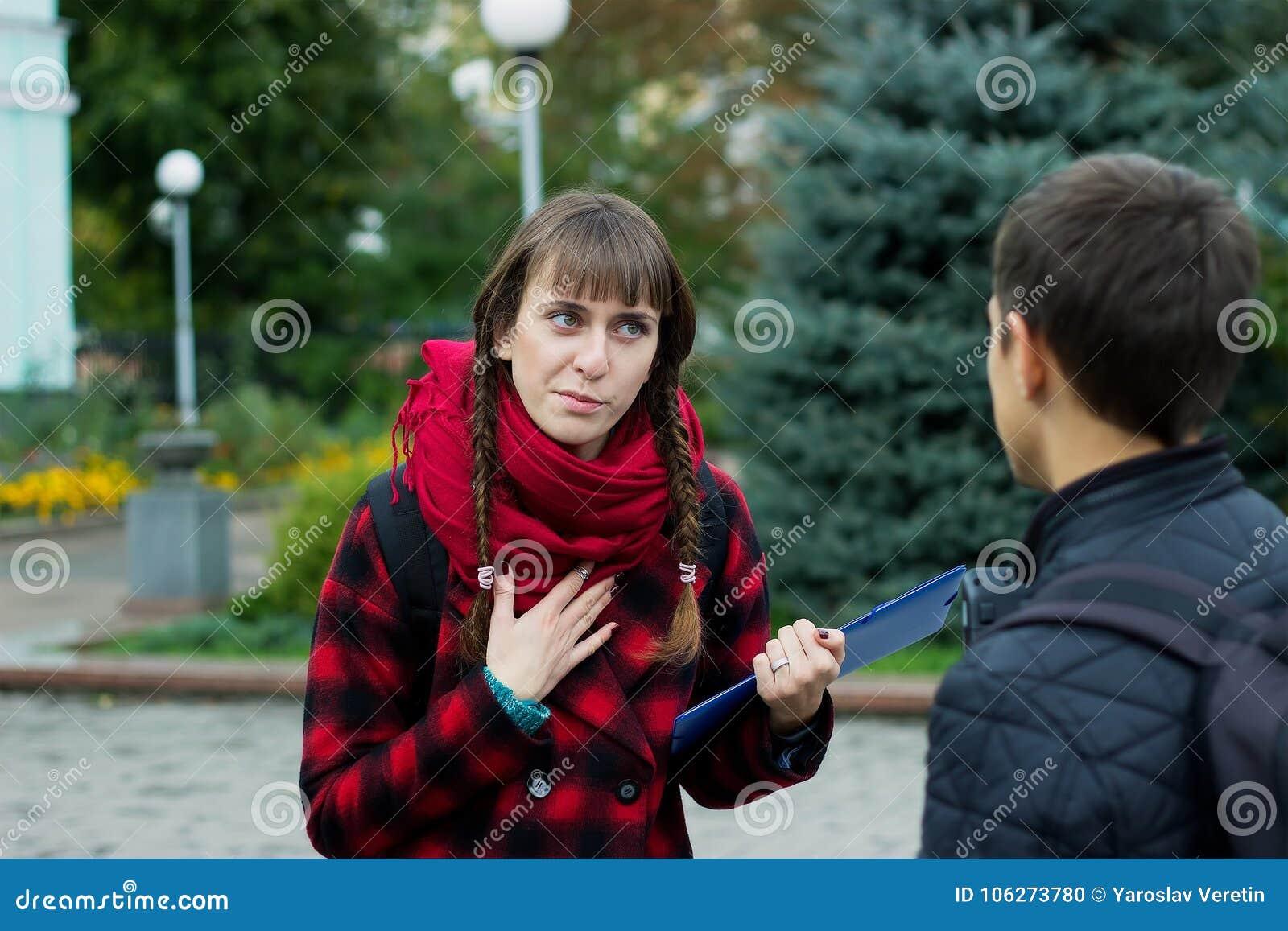年轻学生朋友谈话在学院 证明某事的女孩尝试指向手指